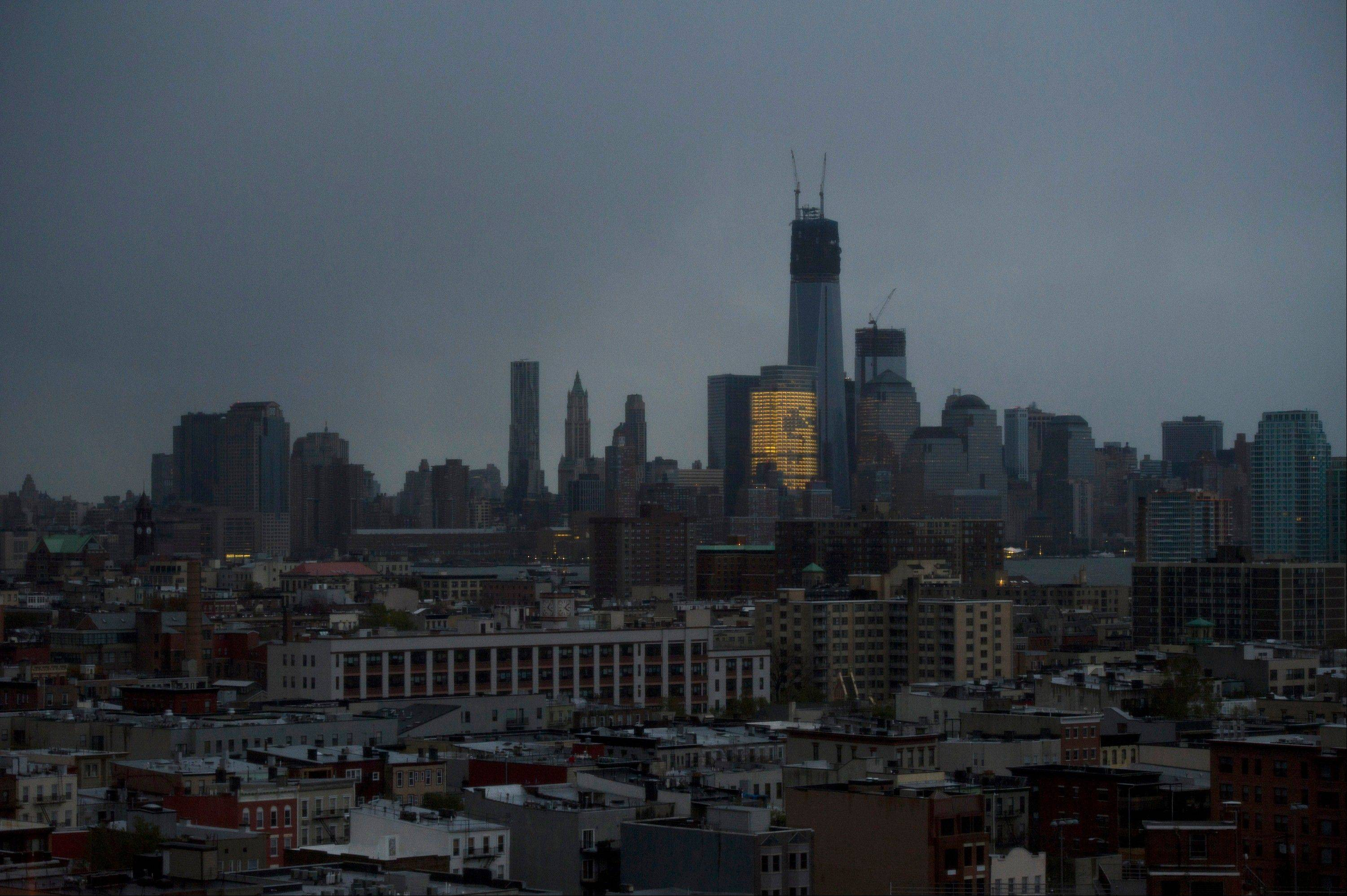 One World Trade Center and large portions of lower Manhattan and Hoboken, N.J., are seen without power from Jersey City, N.J., Tuesday, Oct. 30, 2012, the morning after a powerful storm that started out as Hurricane Sandy made landfall on the East Coast. New York City awakened Tuesday to a flooded subway system, shuttered financial markets and hundreds of thousands of people without power a day after a wall of seawater and high winds slammed into the city, destroying buildings and flooding tunnels.