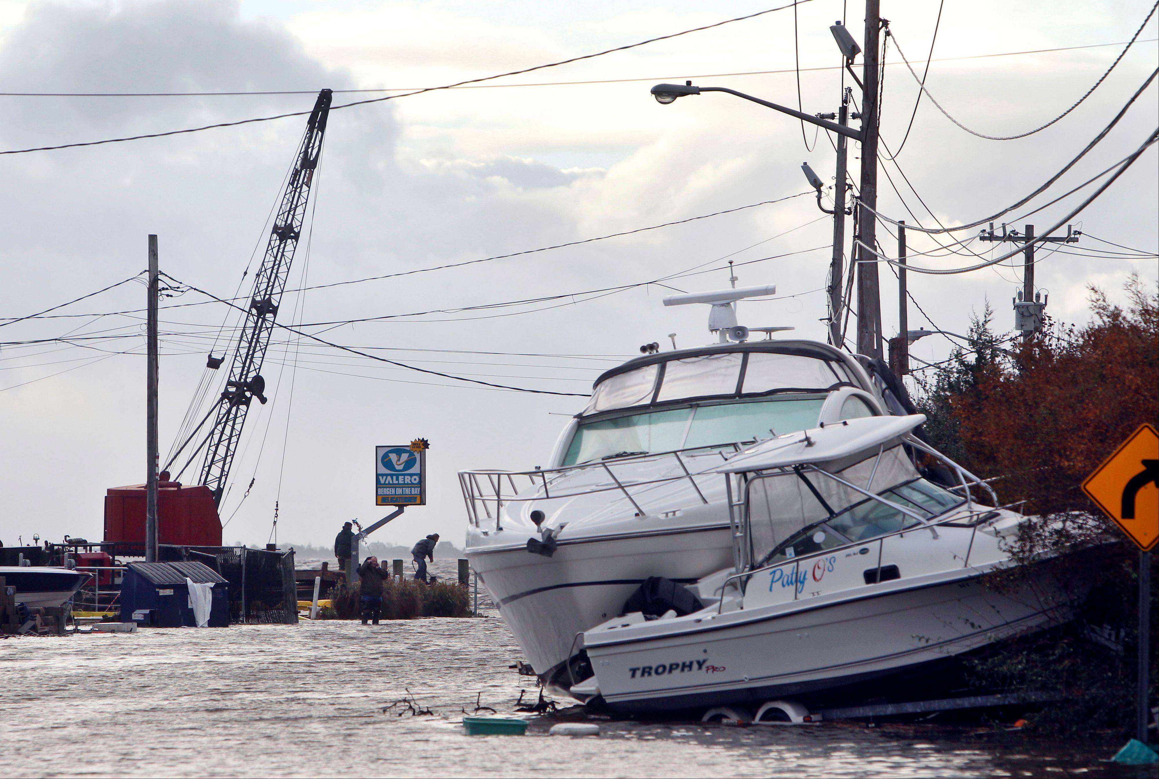 Boats lie piled up as people work to secure a fuel dock in the wake of superstorm Sandy, Tuesday, Oct. 30, 2012, in West Babylon, N.Y. The storm that made landfall in New Jersey on Monday evening with 80 mph sustained winds killed at least 16 people in seven states, cut power to more than 7.4 million homes and businesses from the Carolinas to Ohio, caused scares at two nuclear power plants and stopped the presidential campaign cold.