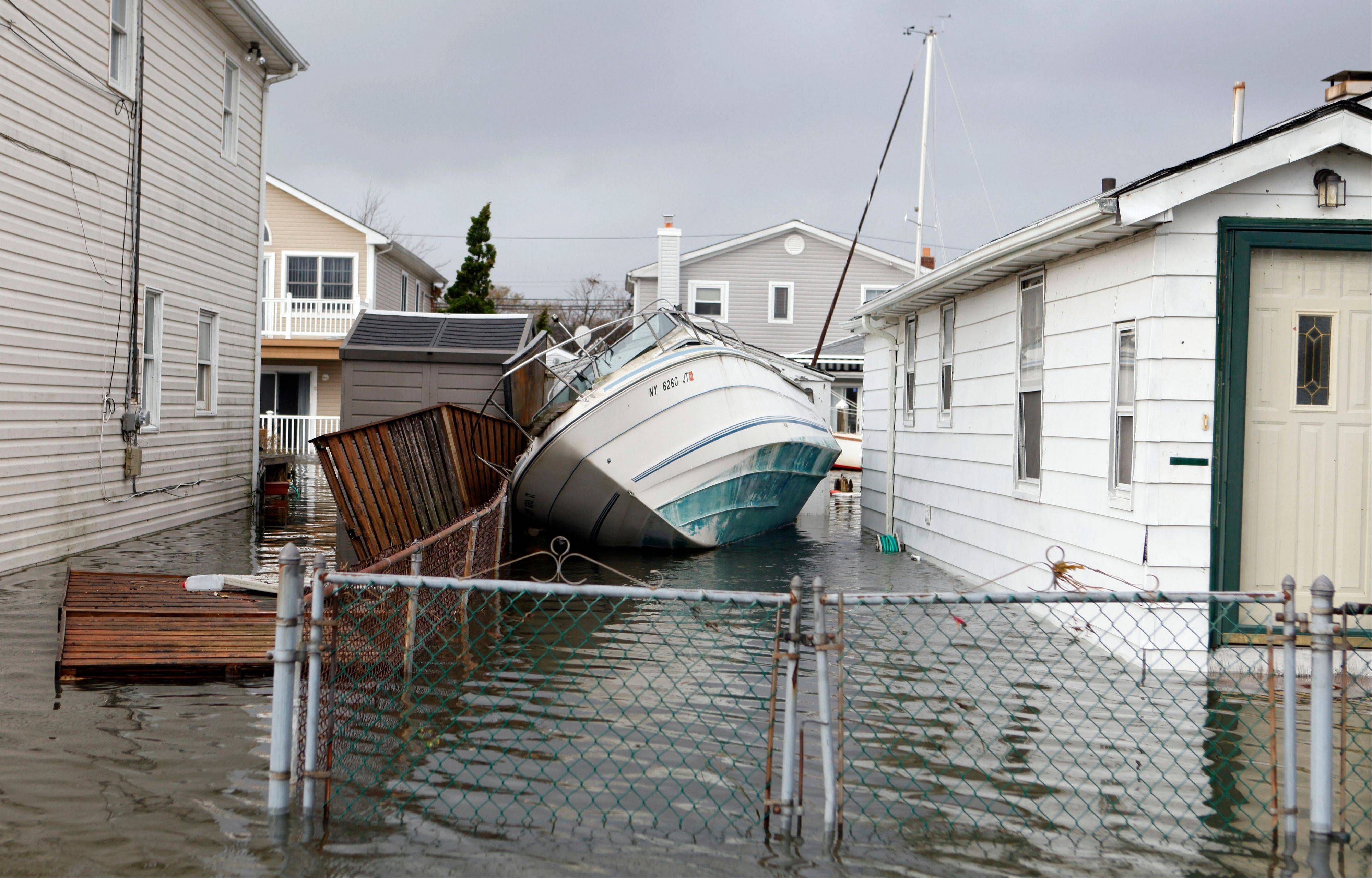 A boat lies toppled between two flooded houses in the aftermath of superstorm Sandy, Tuesday, Oct. 30, 2012, in Lindenhurst, N.Y.
