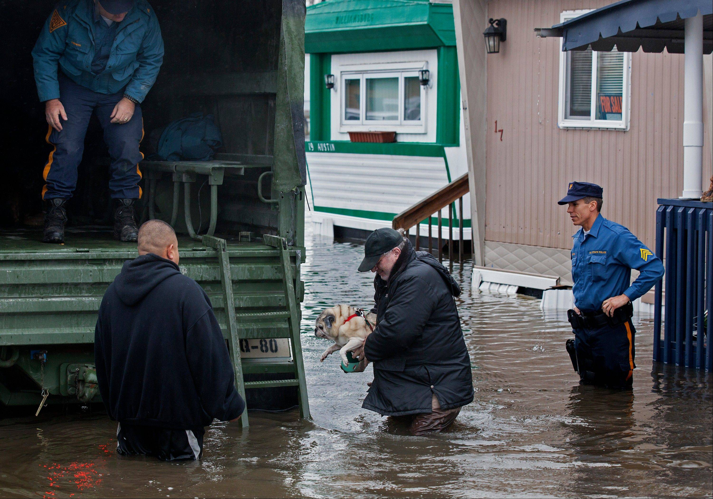 With the aid of New Jersey State Police, a man walks with his dog to a National Guard vehicle after leaving his flooded home at the Metropolitan Trailer Park in Moonachie, N.J., Tuesday, Oct. 30, 2012, in the wake of superstorm Sandy. Sandy arrived along the East Coast and morphed into a huge and problematic system, putting more than 7.5 million homes and businesses in the dark and causing a number of deaths.