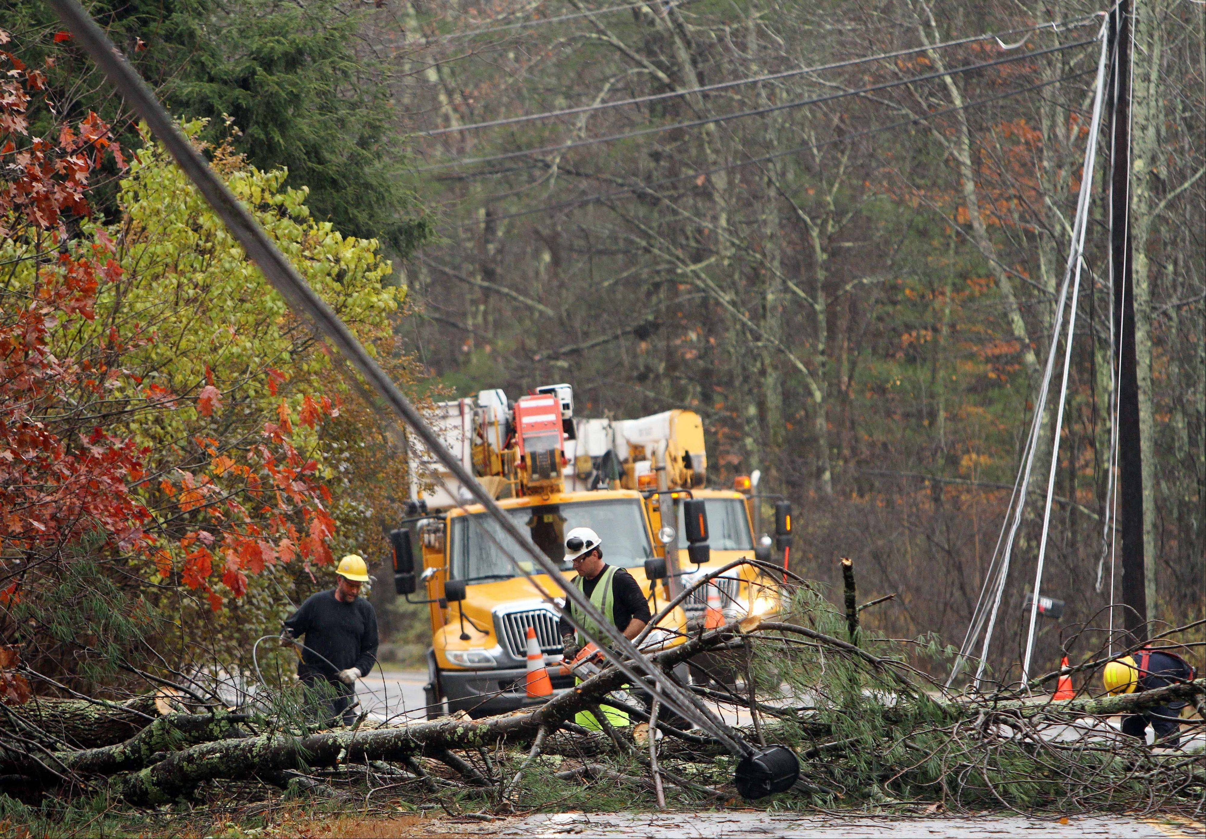 Crews work to clean up downed power lines in the aftermath of superstorm Sandy, Tuesday, Oct. 30, 2012 in Milton, N.H. Thousands of New Hampshire residents and businesses were without power.