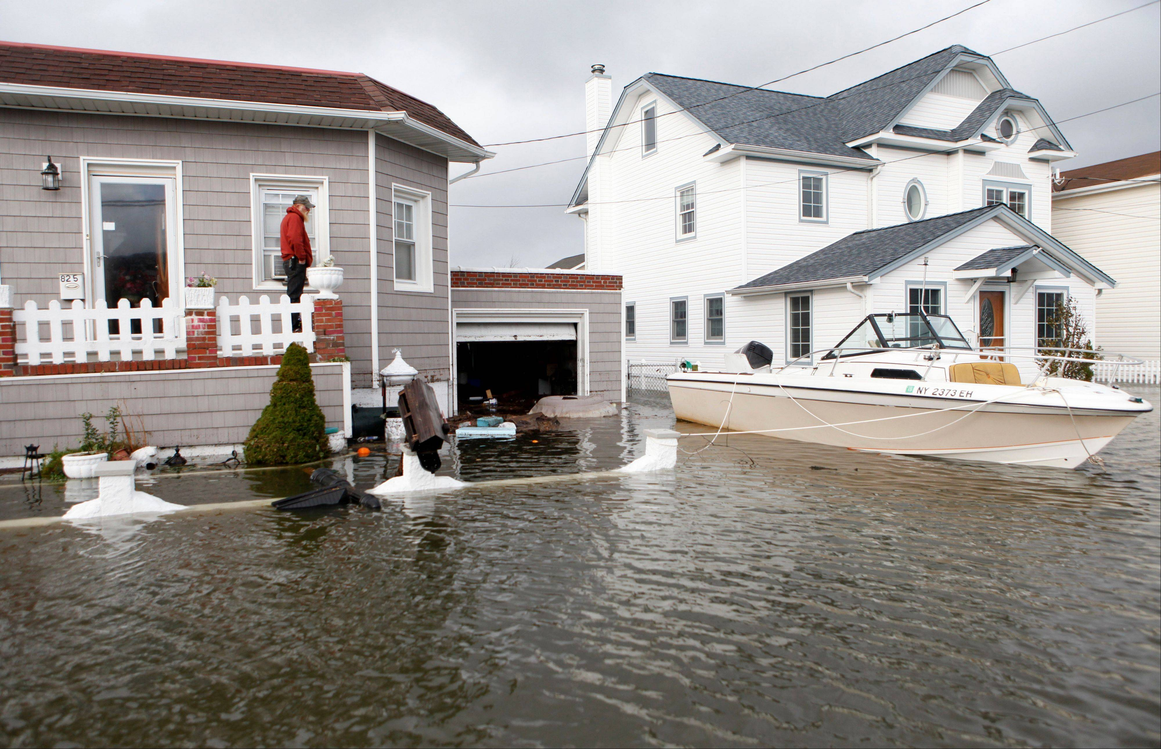 A boat floats in the driveway of a home in the aftermath of superstorm Sandy, Tuesday, Oct. 30, 2012, in Lindenhurst, N.Y.