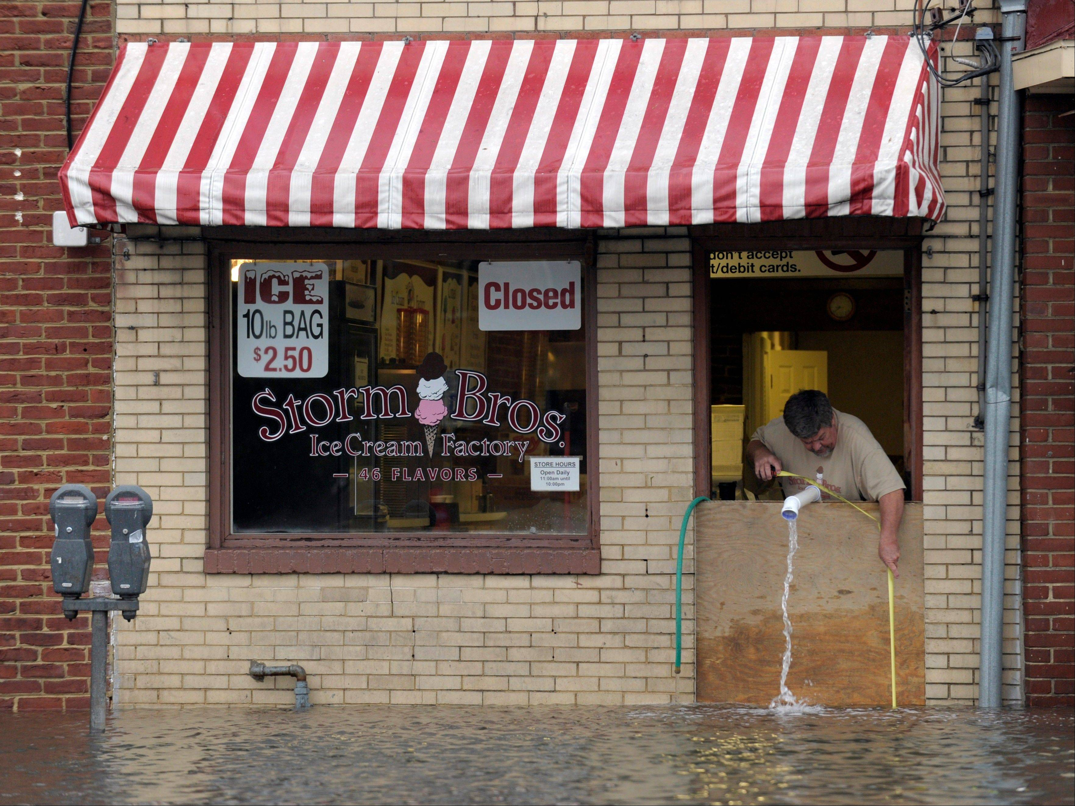 Sveinn Storm, owner of Storm Bros. Ice Cream Factory measures the floodwaters outside his store in Annapolis, Md., Tuesday, Oct. 30, 2012, in the aftermath of Superstorm Sandy that passed through the East Coast.