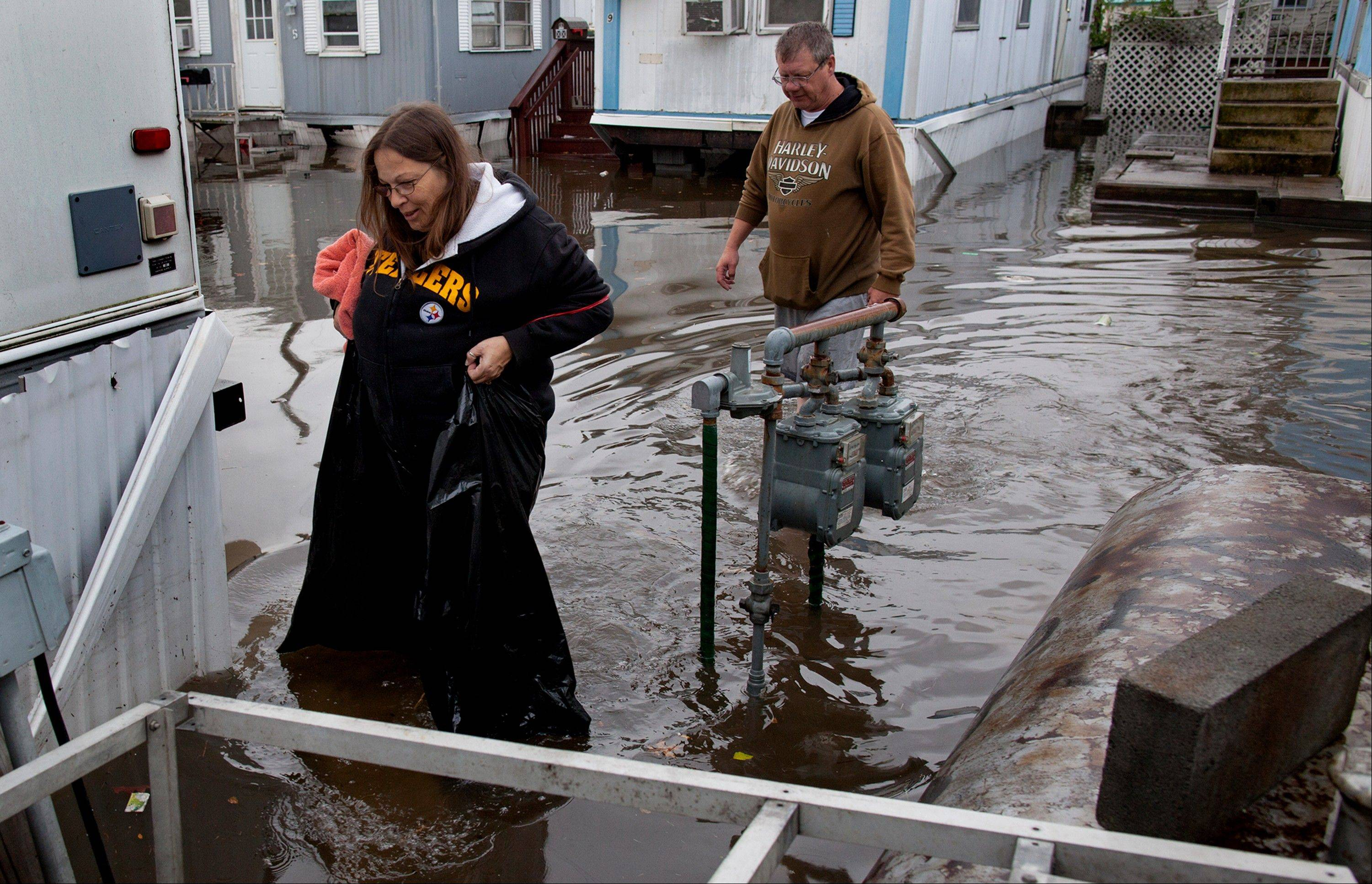 Using garbage bags to keep her waist dry, Mary Ann Tobias, and Walter Chaney of Moonachie, N.J. walk from their flooded home in the Metropolitan Trailer Park in Moonachie, N.J. Tuesday, Oct. 30, 2012 in the wake of superstorm Sandy.
