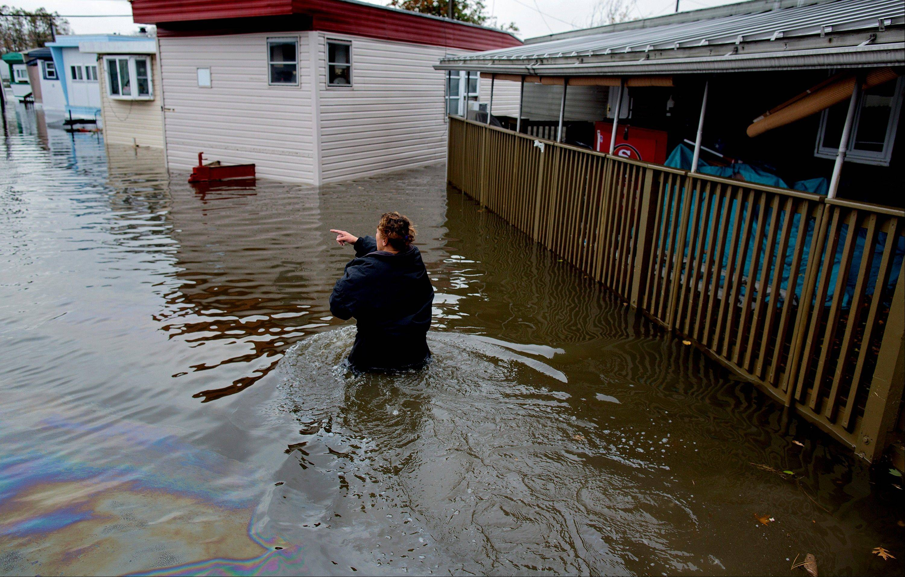 Andrea Grolon walks through waist-deep water in the Metropolitan Trailer Park in Moonachie, N.J. on Tuesday, Oct. 30, 2012. Grolon, a resident of the trailer park, was wading through oil covered water to help others get to rescue vehicles in the wake of superstorm Sandy.