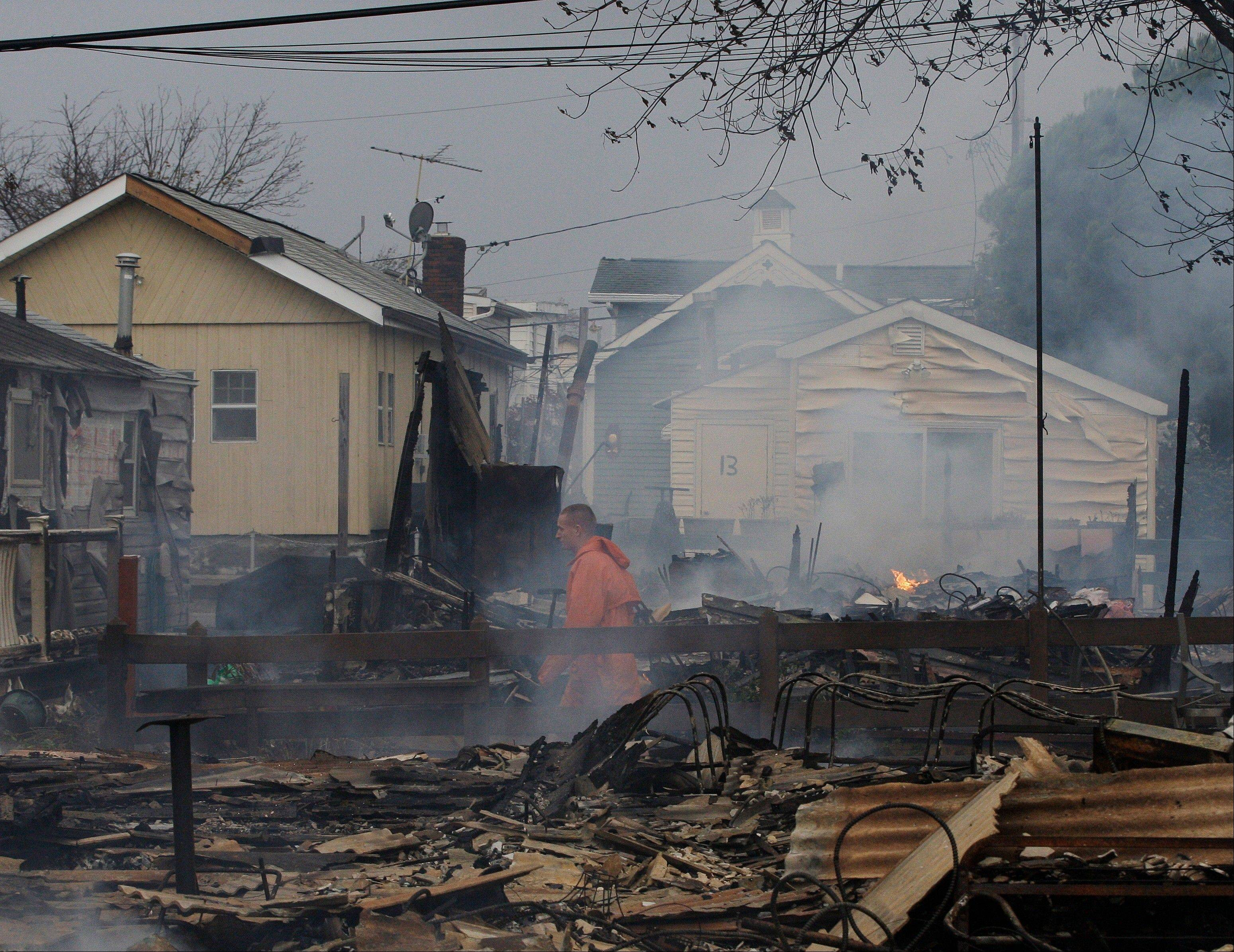 Keith Klein walks through homes damaged by a fire at Breezy Point in the New York City borough of Queens. Tuesday, Oct. 30, 2012. The fire destroyed between 80 and 100 houses Monday night in an area flooded by the superstorm that began sweeping through earlier.