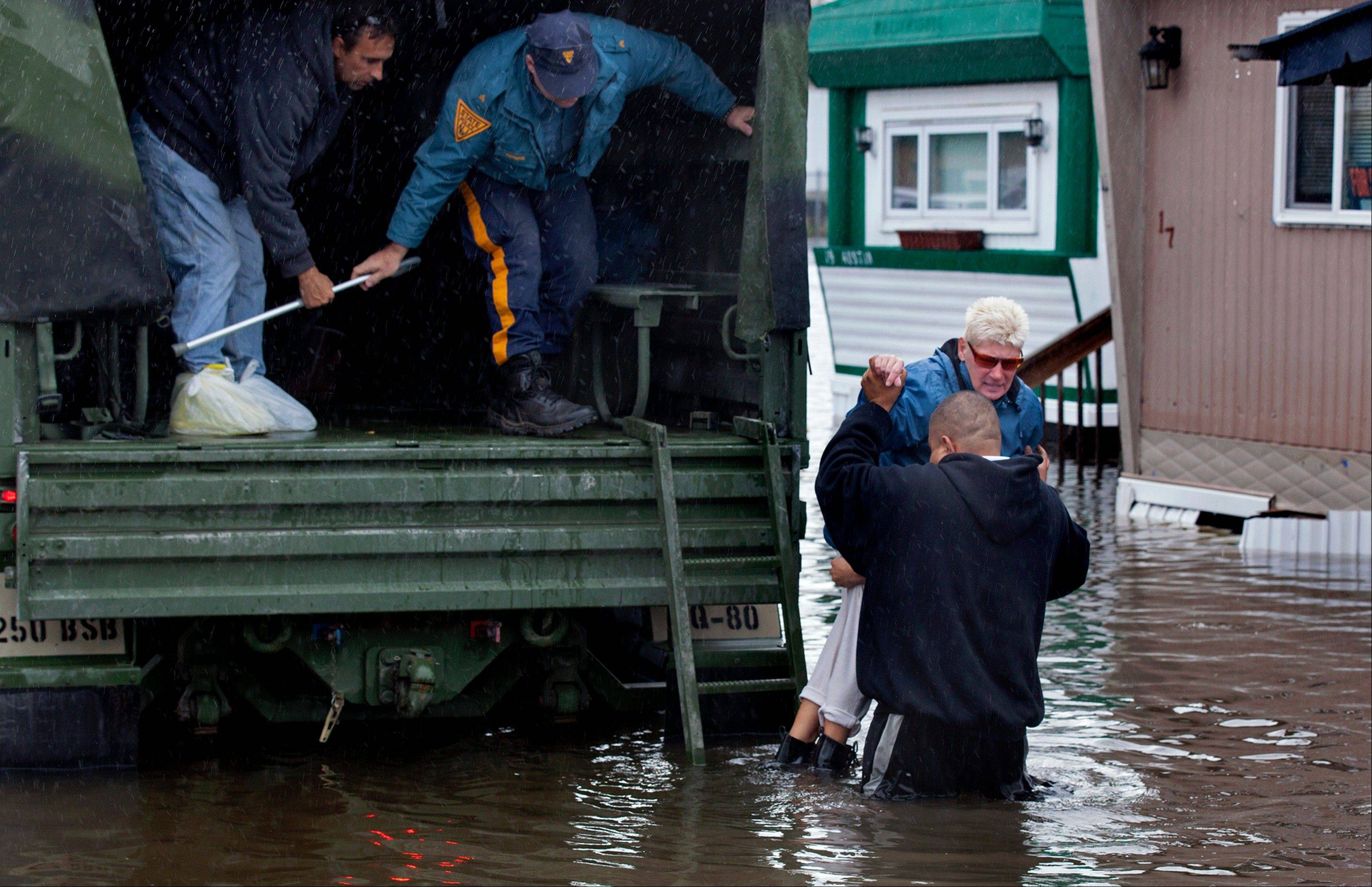 A woman is lifted into a National Guard vehicle after leaving her flooded home at the Metropolitan Trailer Park in Moonachie, N.J. Tuesday, Oct. 30, 2012, after supsterstorm Sandy. Sandy, which was downgraded from hurricane just before making landfall, caused multiple fatalities, halted mass transit and cut power to more than 6 million homes and businesses.