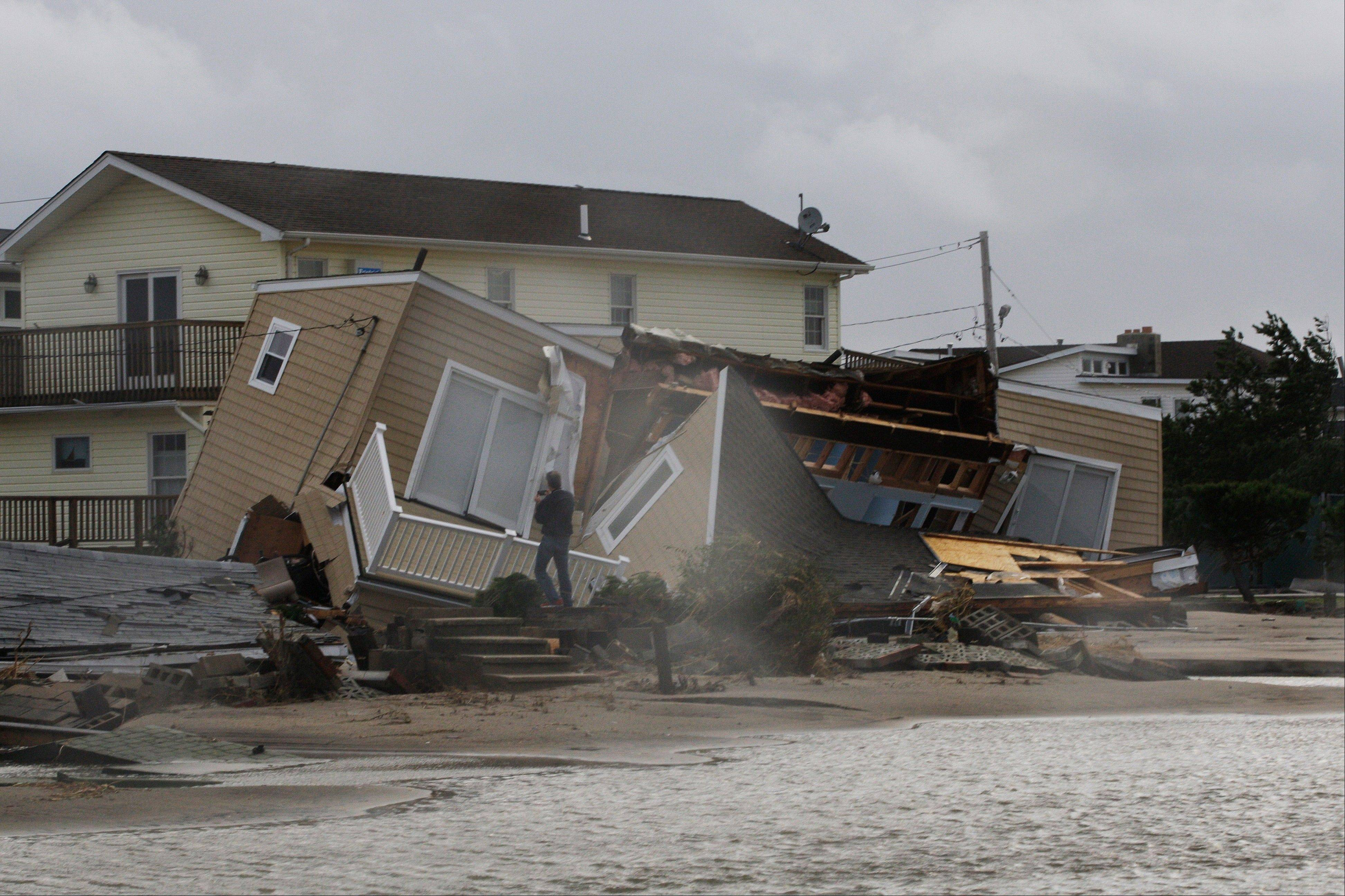 A man photographs a home damaged during a storm at Breezy Point in the New York City borough of Queens Tuesday, Oct. 30, 2012. The fire destroyed between 80 and 100 houses Monday night in an area flooded by the superstorm that began sweeping through earlier.