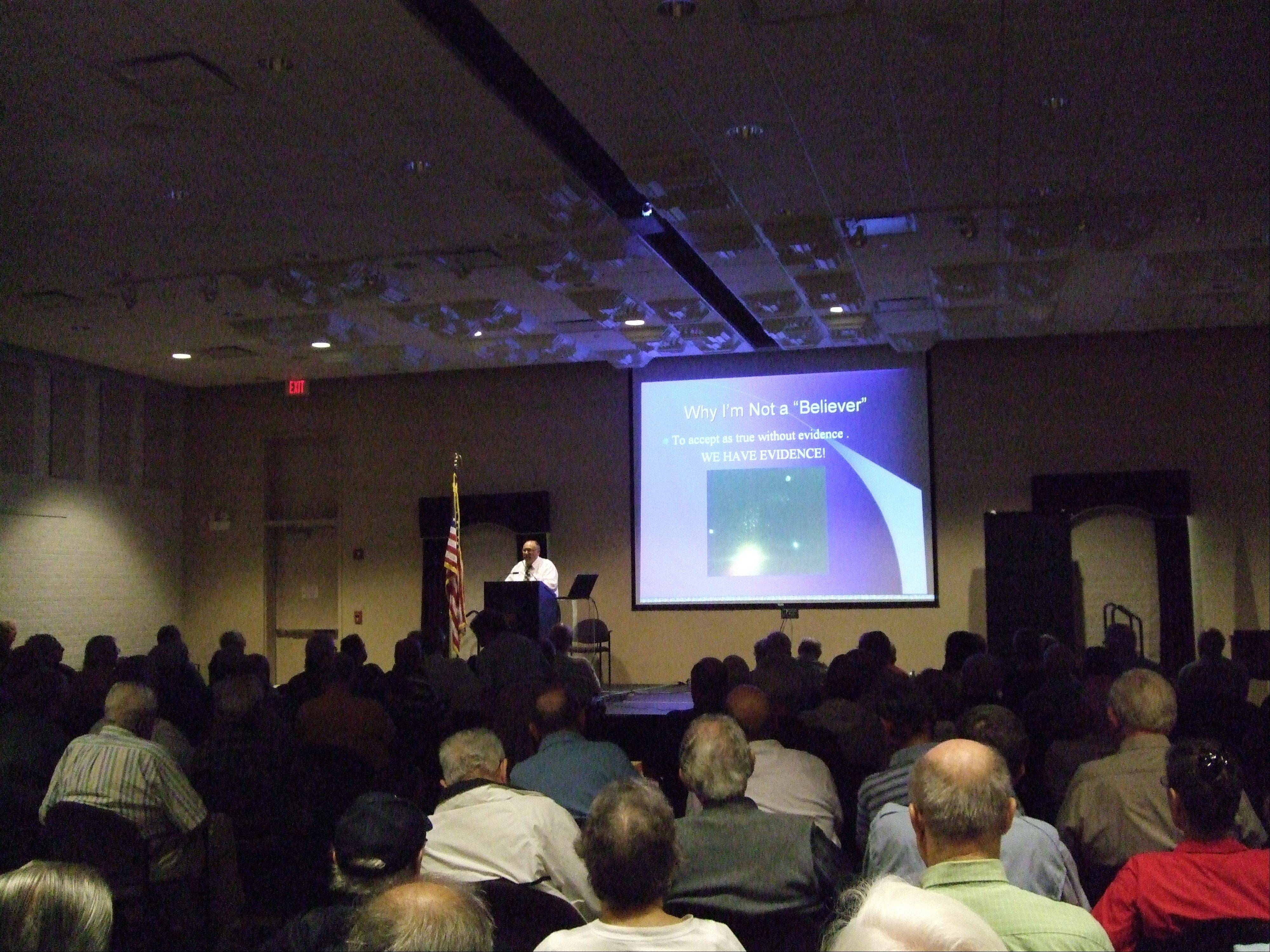 Sam Maranto, state director of the Mutual UFO Network, speaking on UFOs before a large group in the North Shore area.