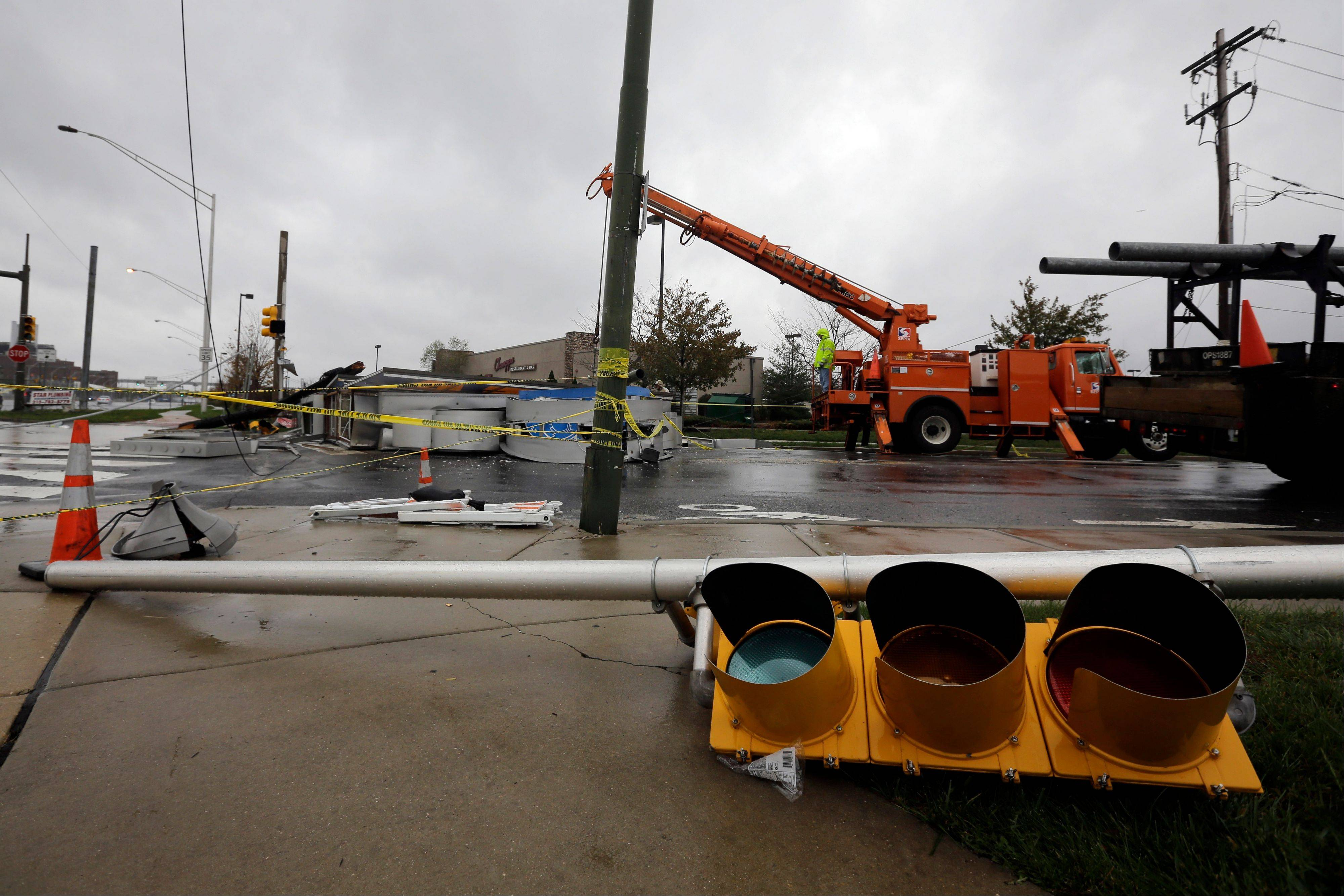 Crews work to remove a damaged sign in the wake of superstorm Sandy, Tuesday, Oct. 30, 2012, in Philadelphia.
