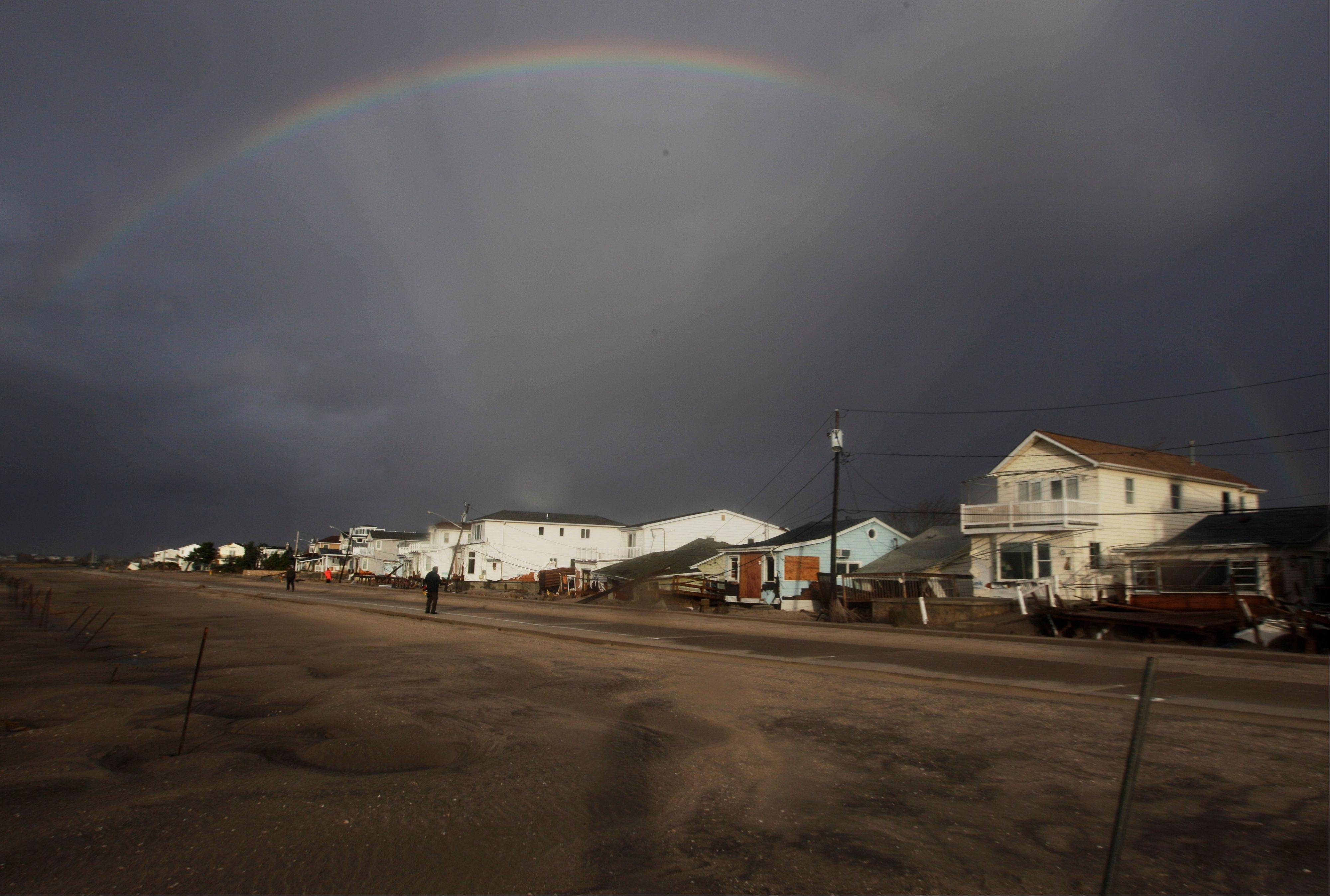 A rainbow forms over Breezy Point in the New York City borough of Queens, in the aftermath of superstorm Sandy, Tuesday, Oct. 30, 2012, in New York. The fire destroyed between 80 and 100 houses Monday night in the flooded neighborhood.