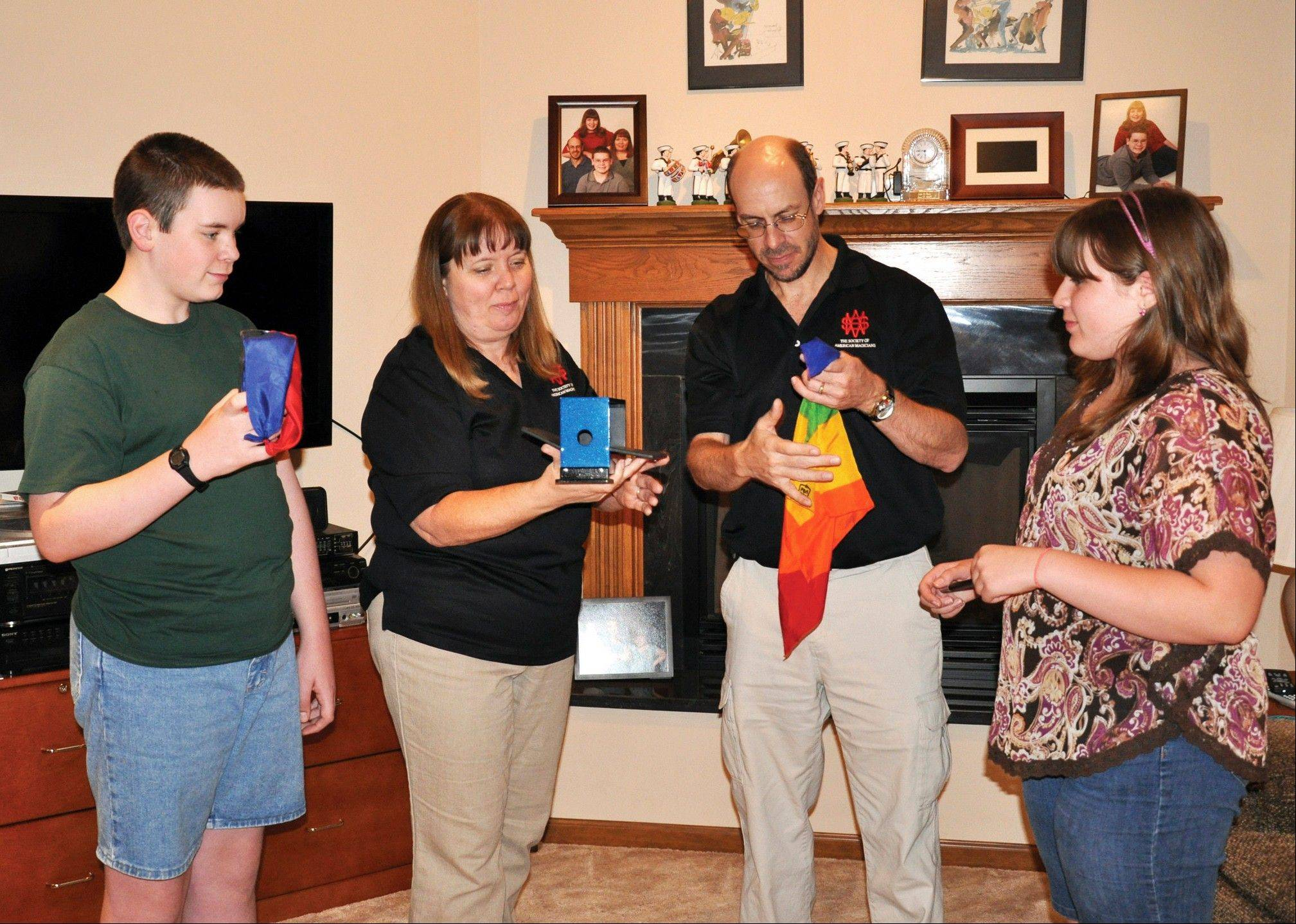 The Bontjes family members, from left, John, Julie, Christopher and Jil, practice magic tricks in the living room of their home in Westville