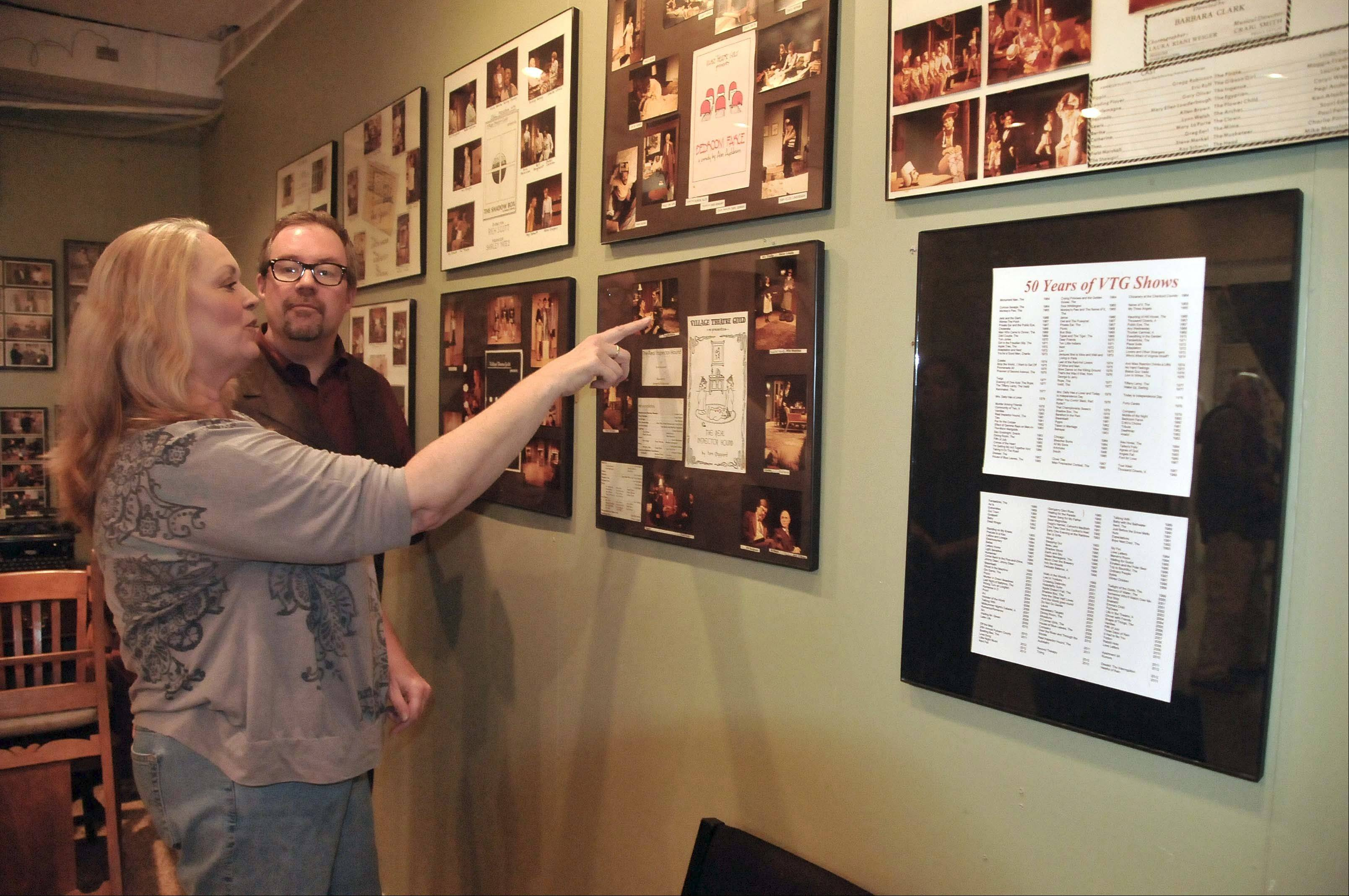 Doug Orlyk and Karen Bronson reminisce over photos of past musicals performed at the Village Theatre in Glen Ellyn.