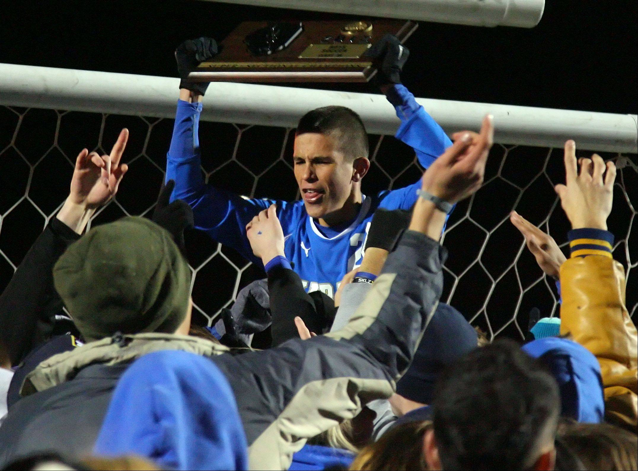Warren's Karl Bappert hoists the super sectional trophy after beating St. Charles East 2-1Tuesday night at Barrington High School.