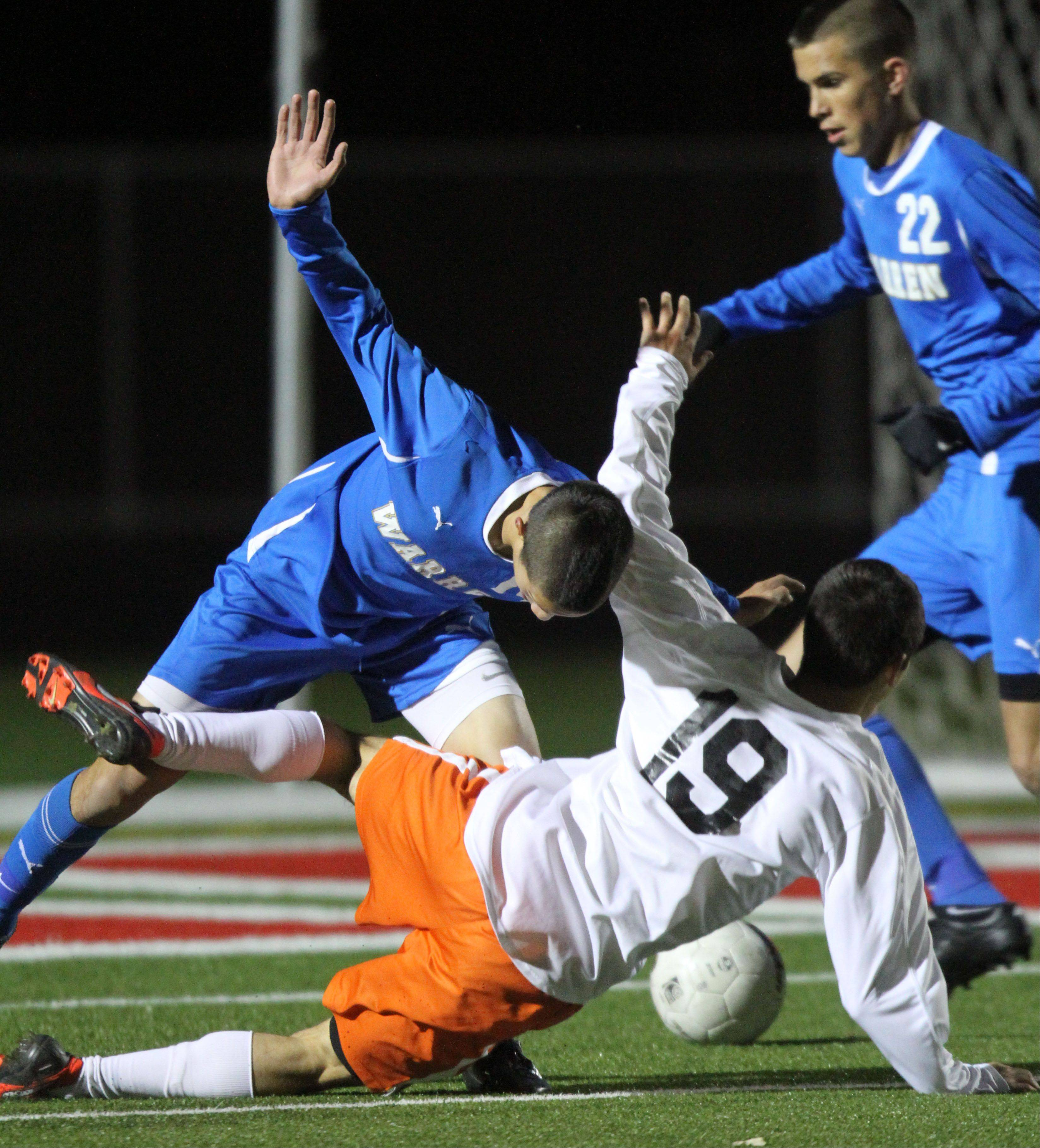 Warren's Nick Haas, left, and St. Charles East's Kevin Kurtz get tangled up during super sectional soccer action Tuesday night at Barrington High School.