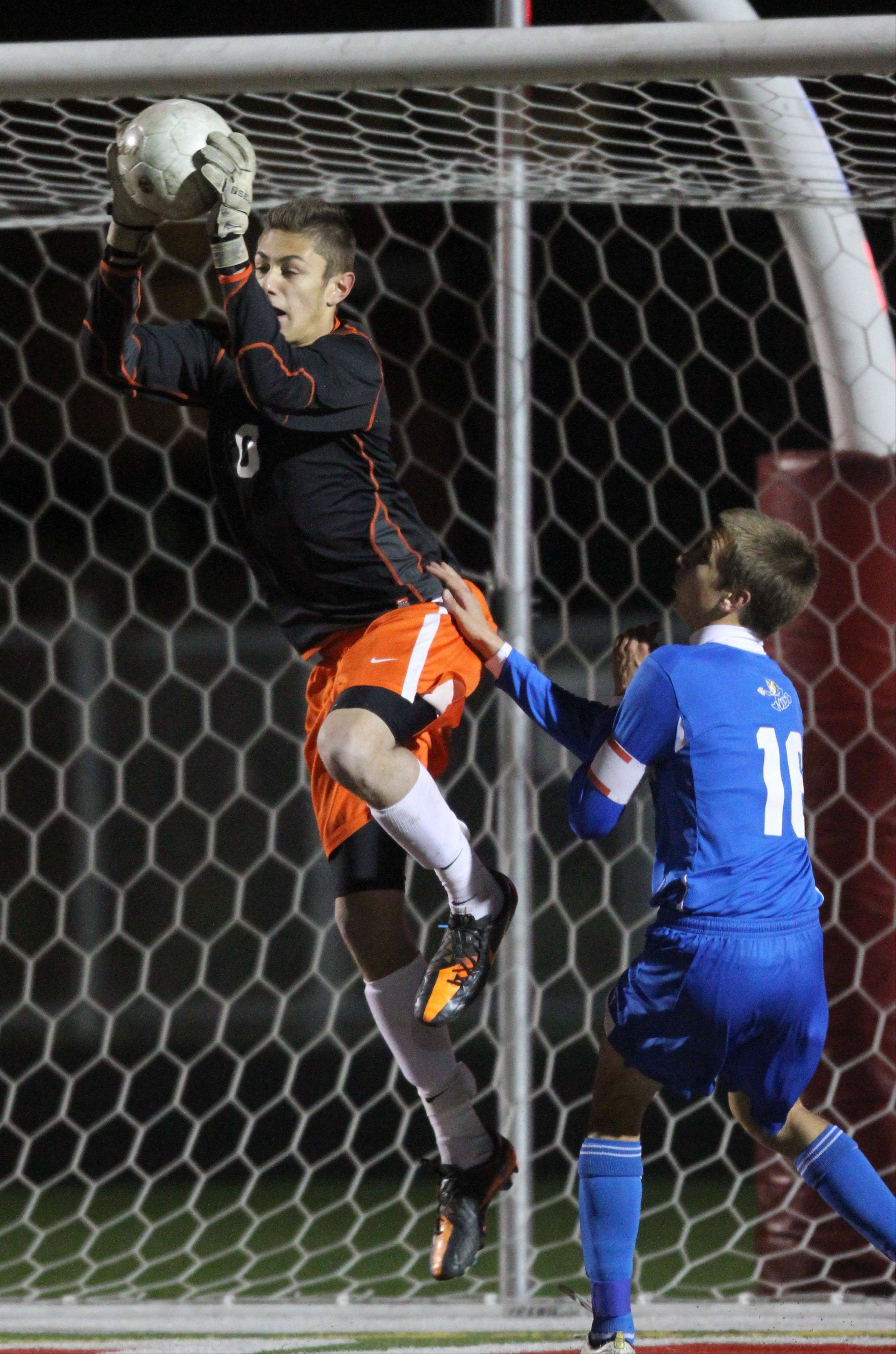 St. Charles East's Chris Locatorto pulls down the bal with Warren's Timmy Pieper pressuring during super sectional soccer action Tuesday night at Barrington High School.