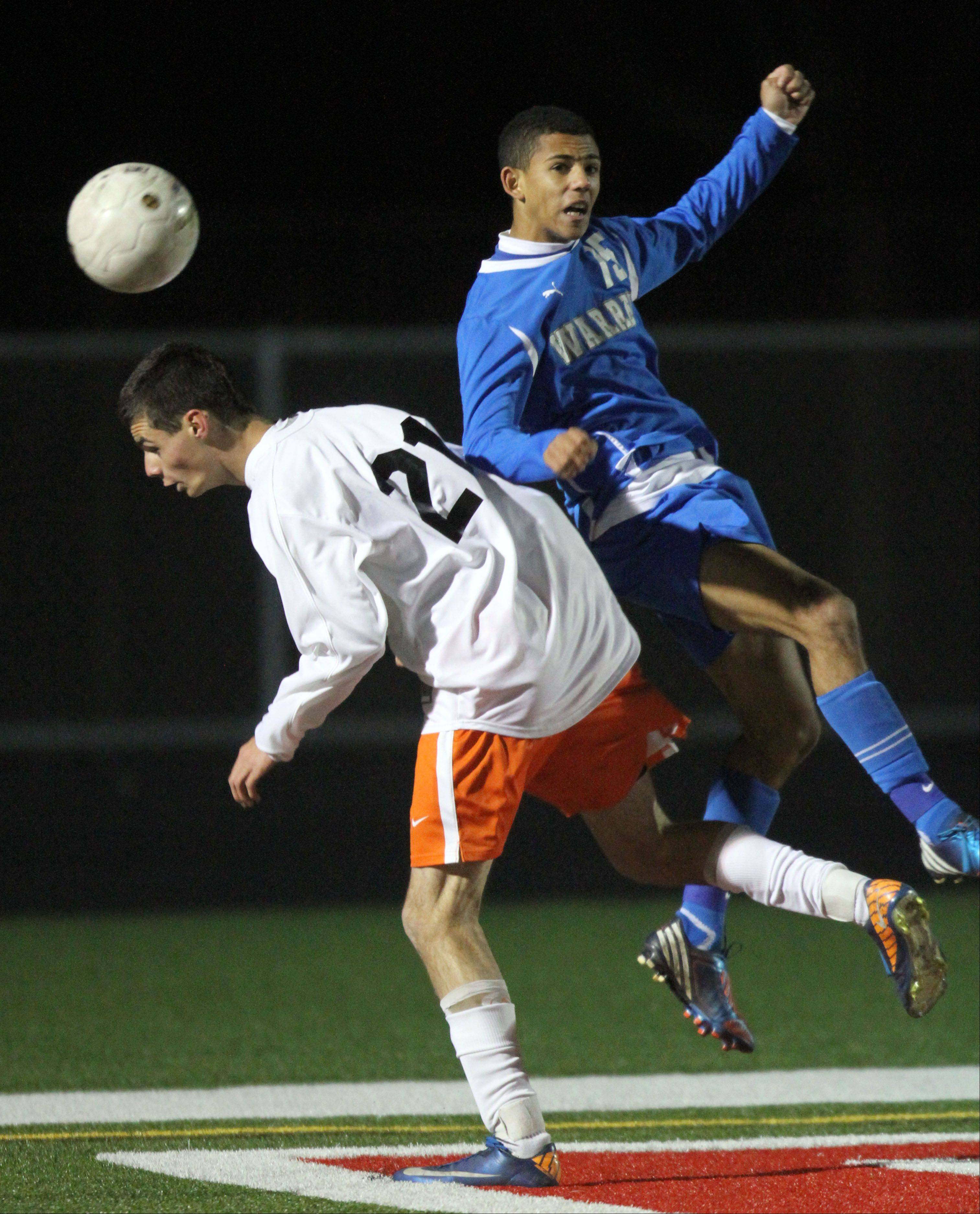 St. Charles East's Daniel DiLeonardi, left and Warren's Elijah Parker battle for the ball during super sectional soccer action Tuesday night at Barrington High School.
