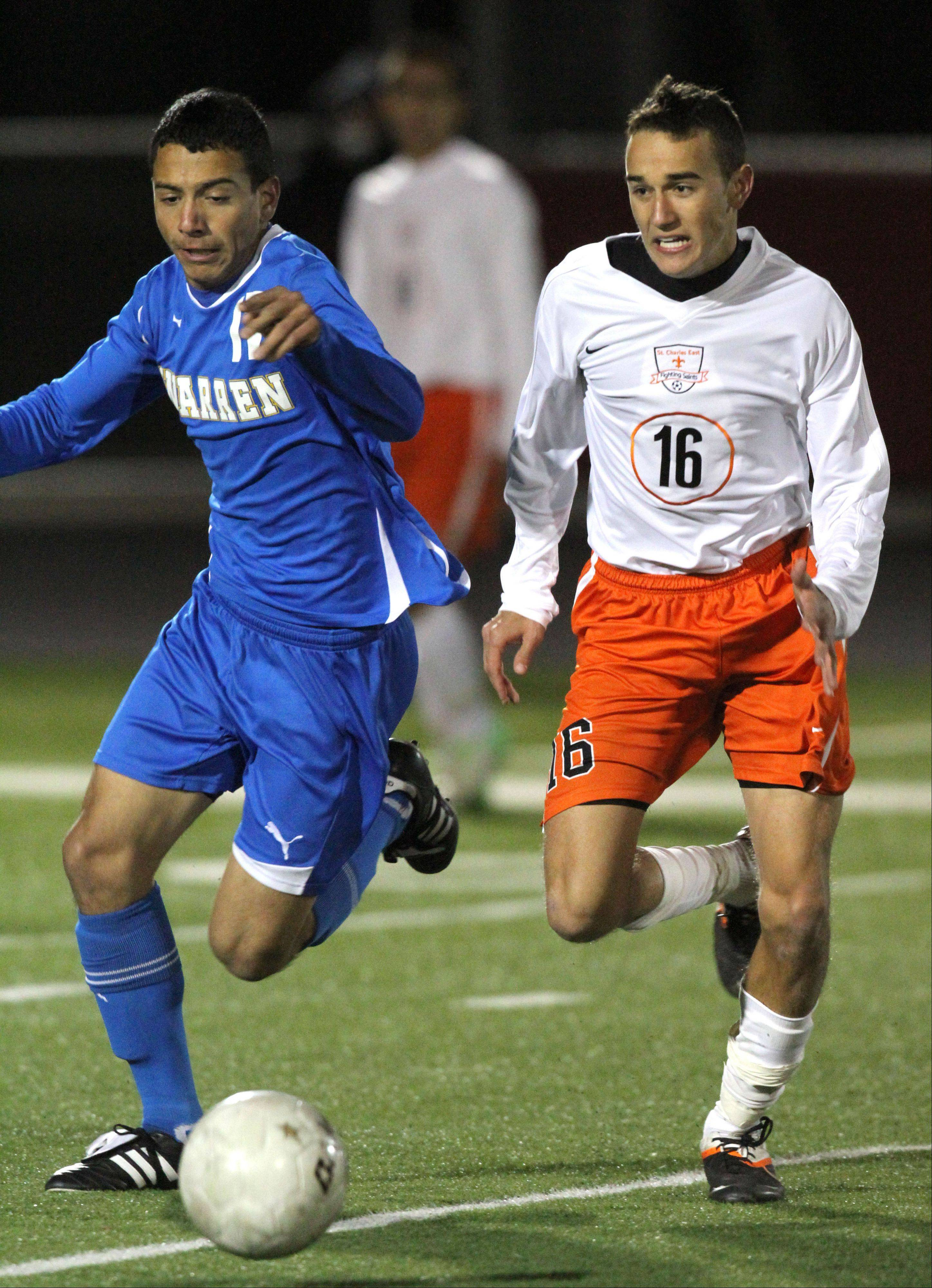 Warren's Rafa Macias, left, and St. Charles East's Jordan Moore battle for the ball during super sectional soccer action Tuesday night at Barrington High School.