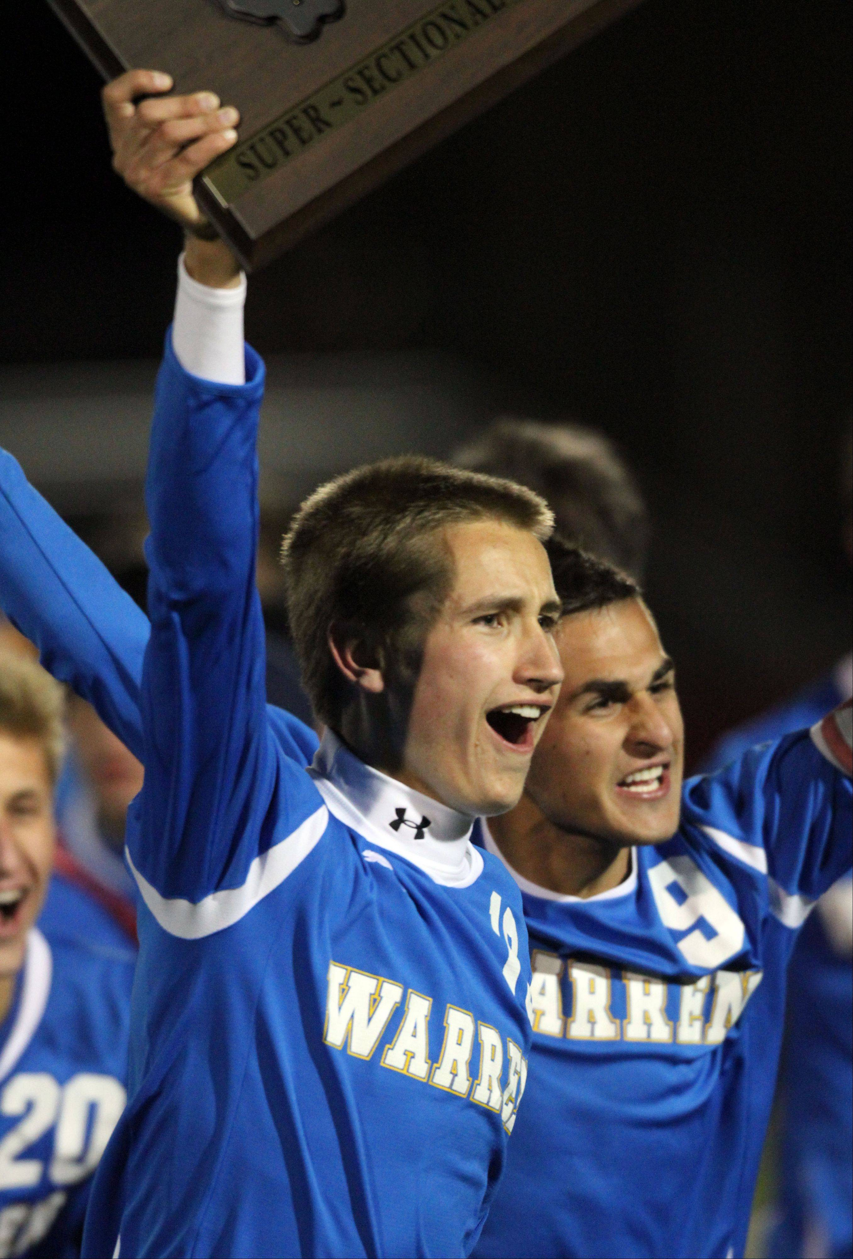 Warren's Timmy Pieper, left and Daniel Szczepanek hoist the super sectional trophy after beating St. Charles East 2-1Tuesday night at Barrington High School.
