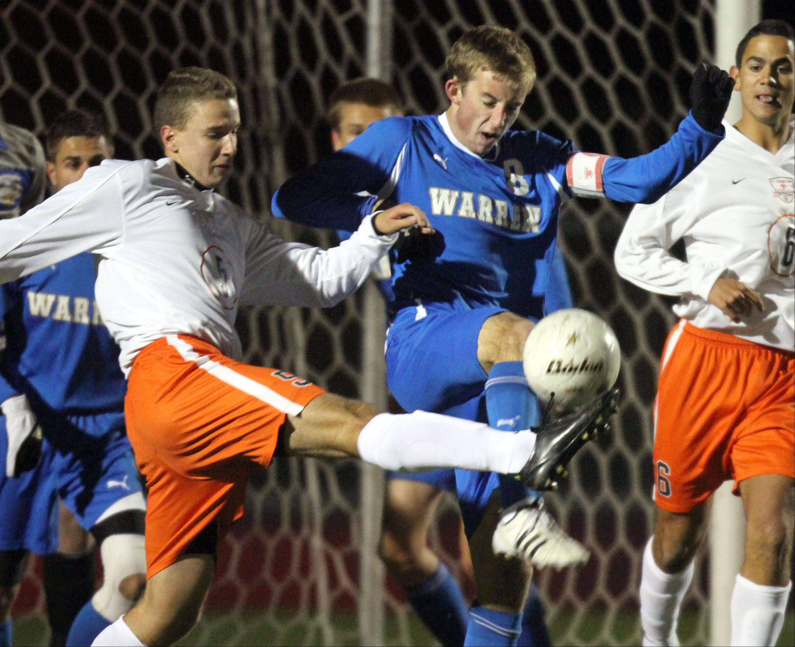 St. Charles East's Ben Womac, left, and Warren's Sean Kirwan battle for the ball during super sectional soccer action Tuesday night at Barrington High School.