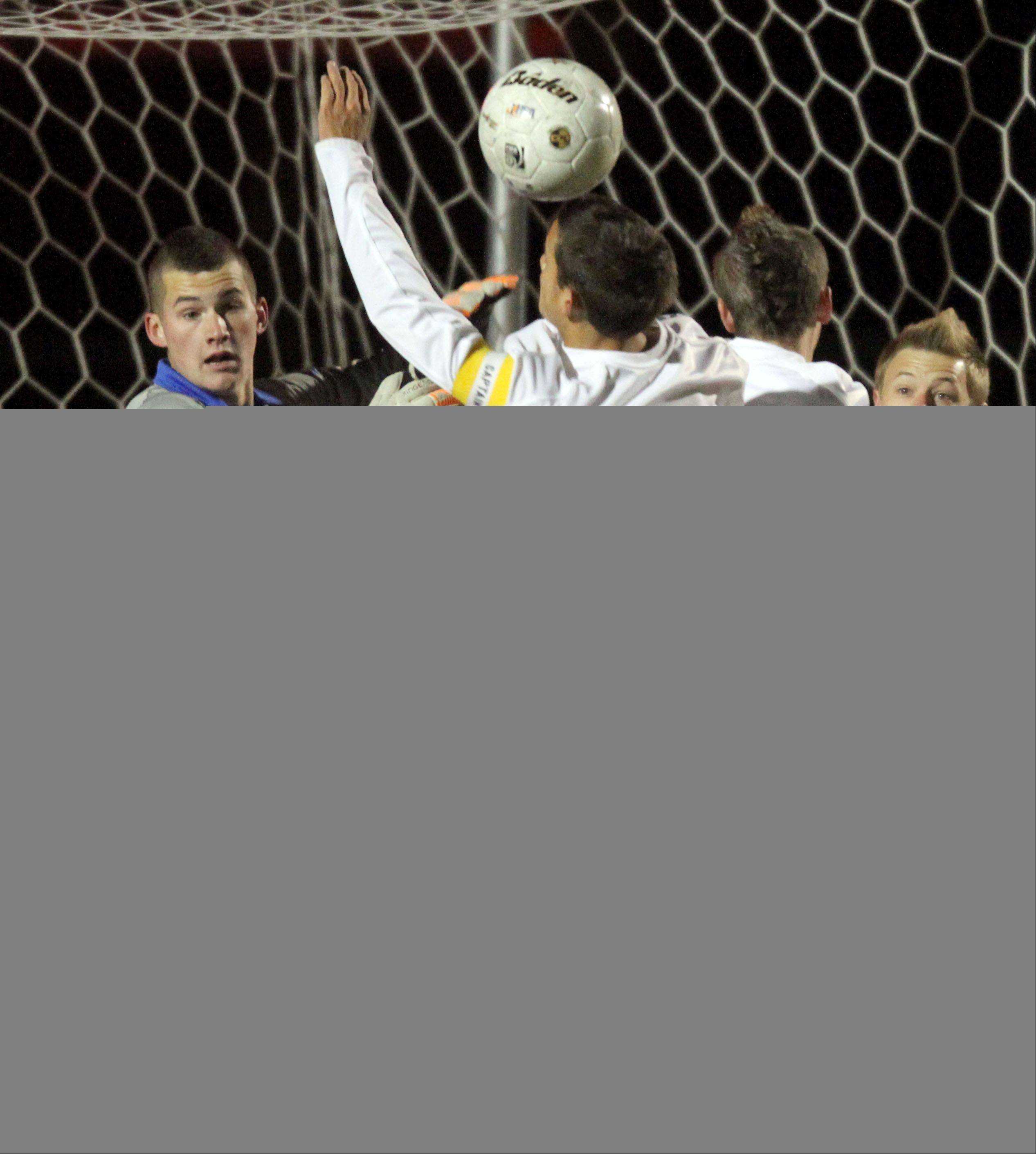 Warren goalie R.J. Hill tires to keep an eye on the ball as players bunch up in front of the net during super sectional soccer action Tuesday night at Barrington High School.