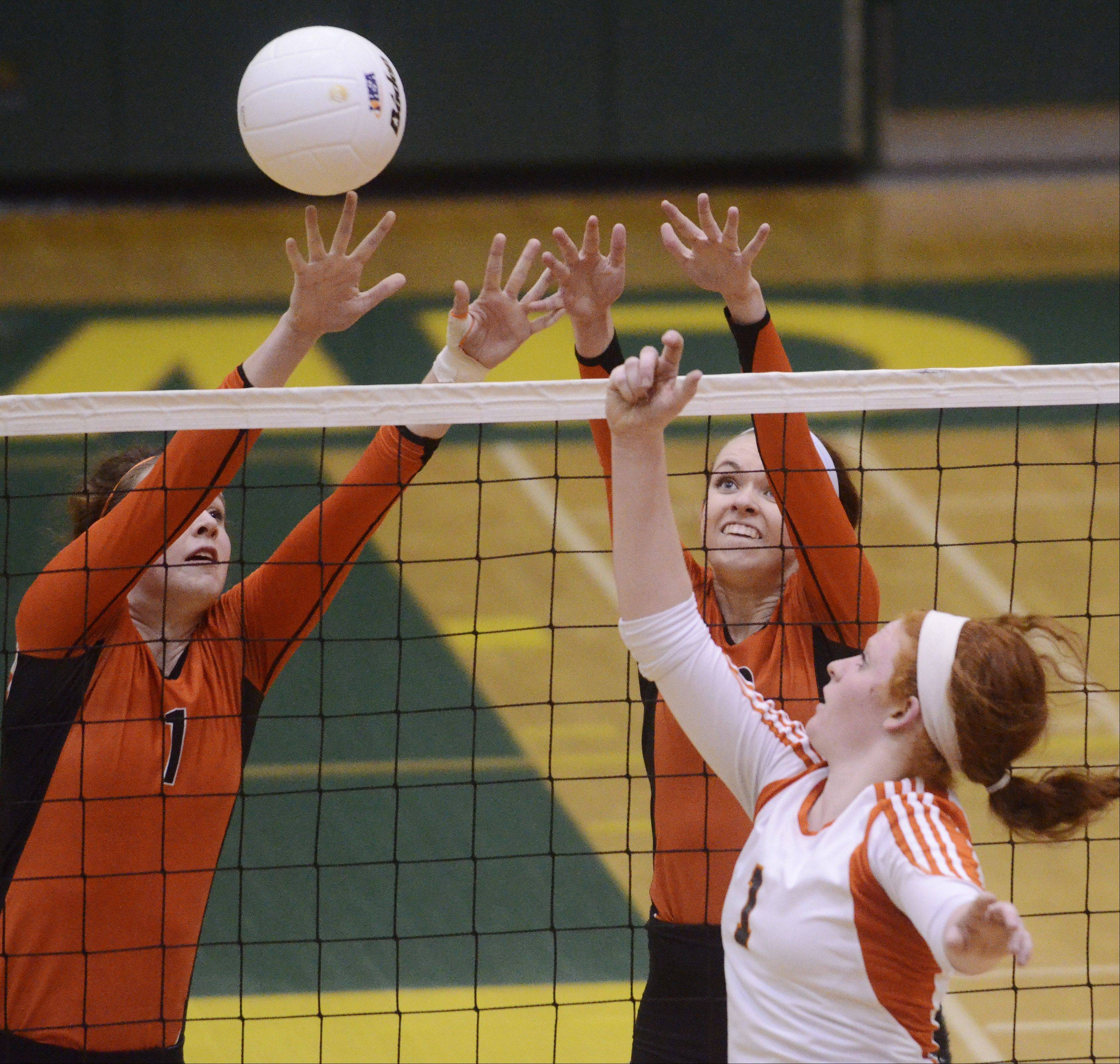 Hersey's Abby Fesl, right, tries to tip the ball past Libertyville's Alex Basler, left, and Rhiannon Prentiss during Tuesday's sectional semifinal at Fremd High School in Palatine.