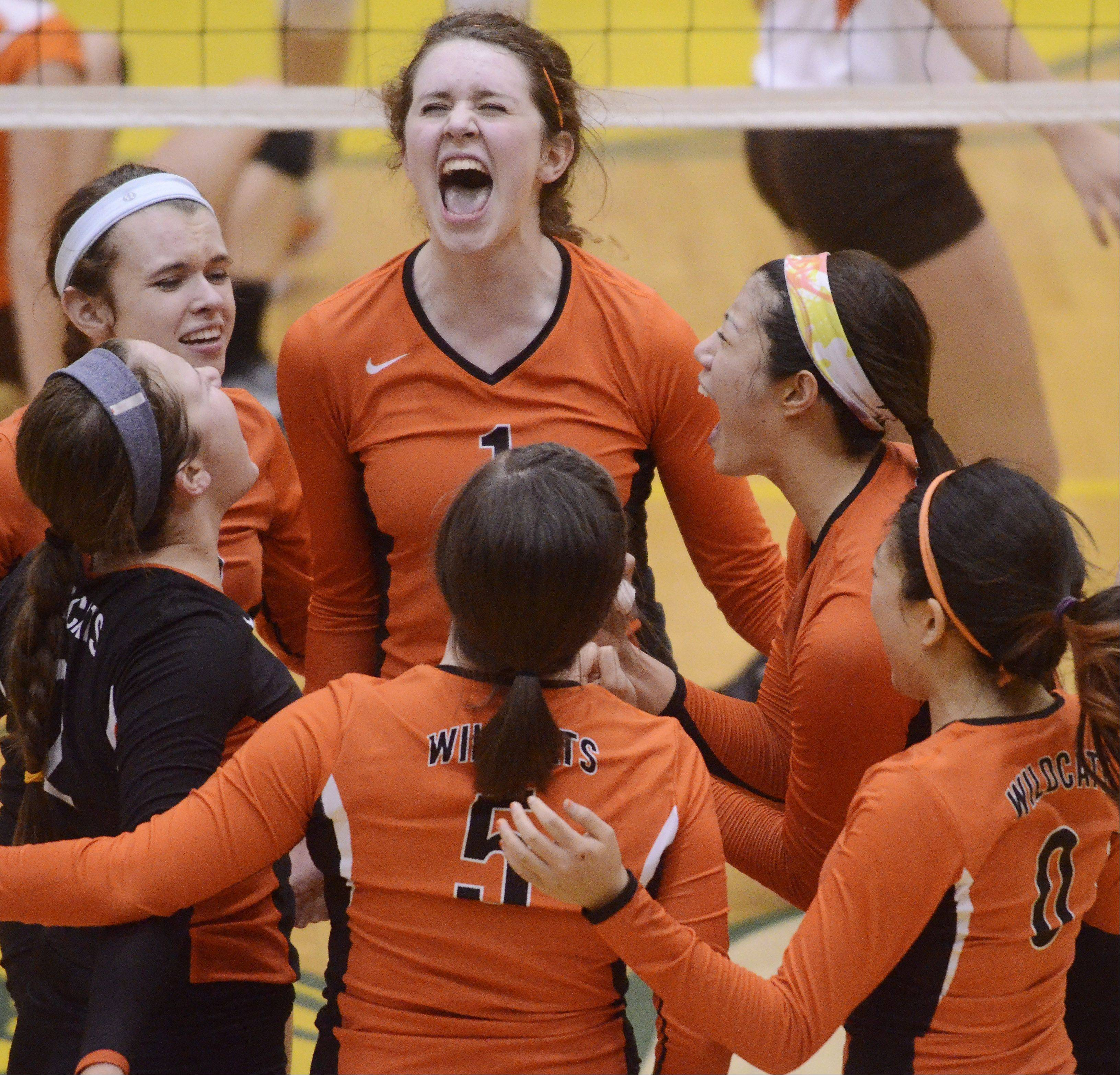 Libertyville volleyball players including Alex Basler, top, begin to celebrate as they close in on Hersey during the third game of during Tuesday's sectional semifinal at Fremd High School in Palatine.