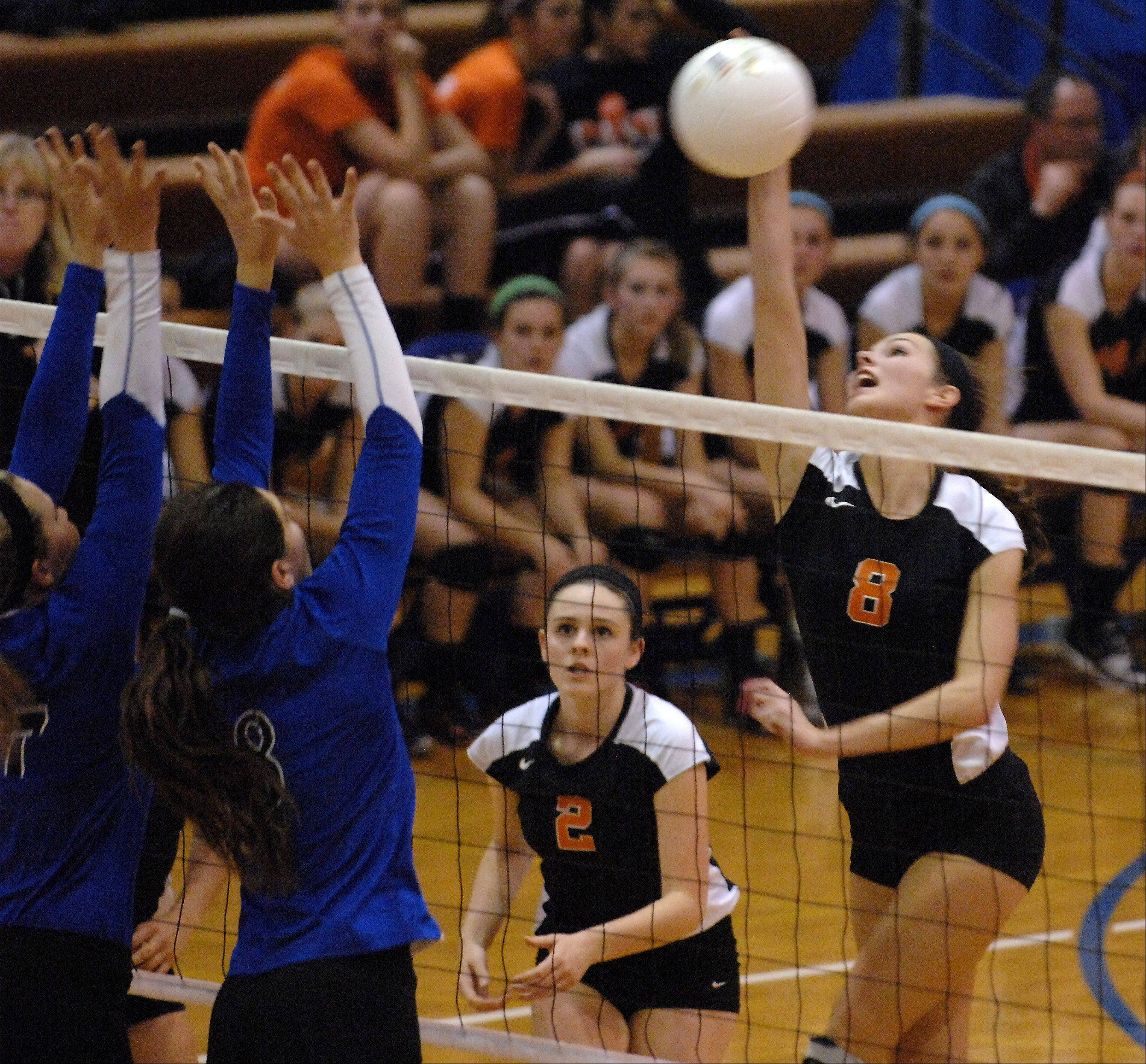 St. Charles East's Emma Johnson tries to hit past a pair of Geneva blockers during Tuesday's sectional semifinals at Larkin High School in Elgin.