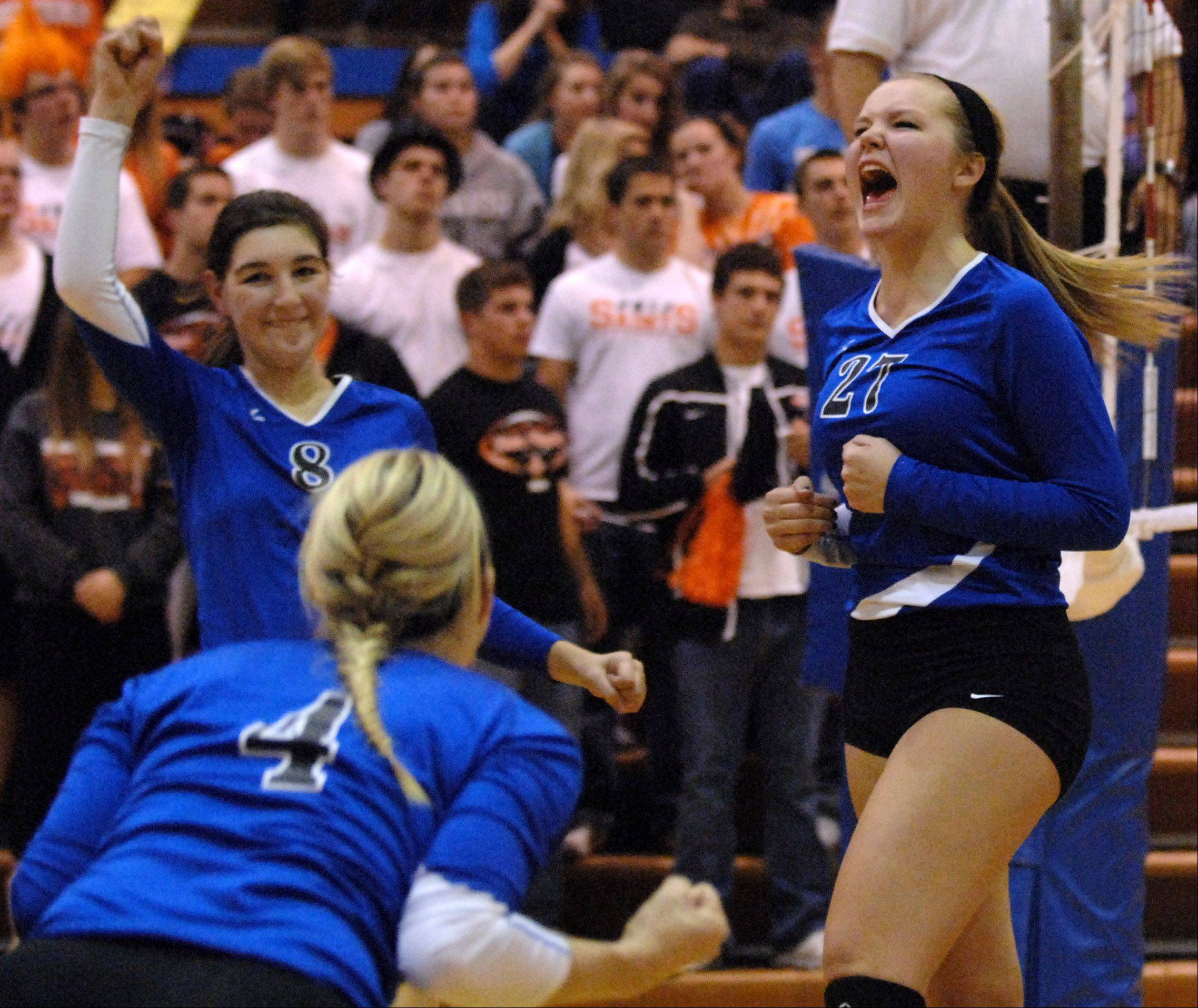 Geneva's Taylor Marmitt (right) and her teammates start to get excited as they get to match point against St. Charles East during Tuesday's sectional semifinals at Larkin High School in Elgin.