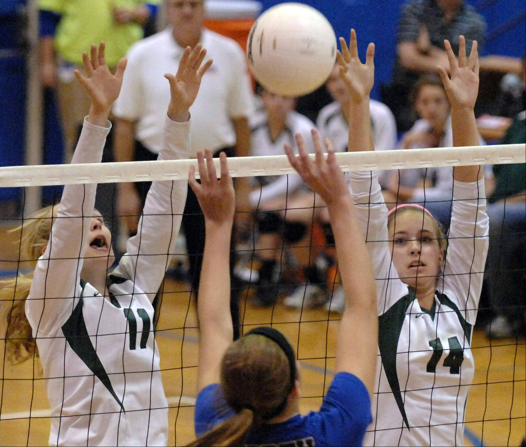 Glenbard West's Caleigh Ryan, left, and Katie Ball go up for a block against St. Charles North during Tuesday's sectional semifinals at Larkin High School in Elgin.
