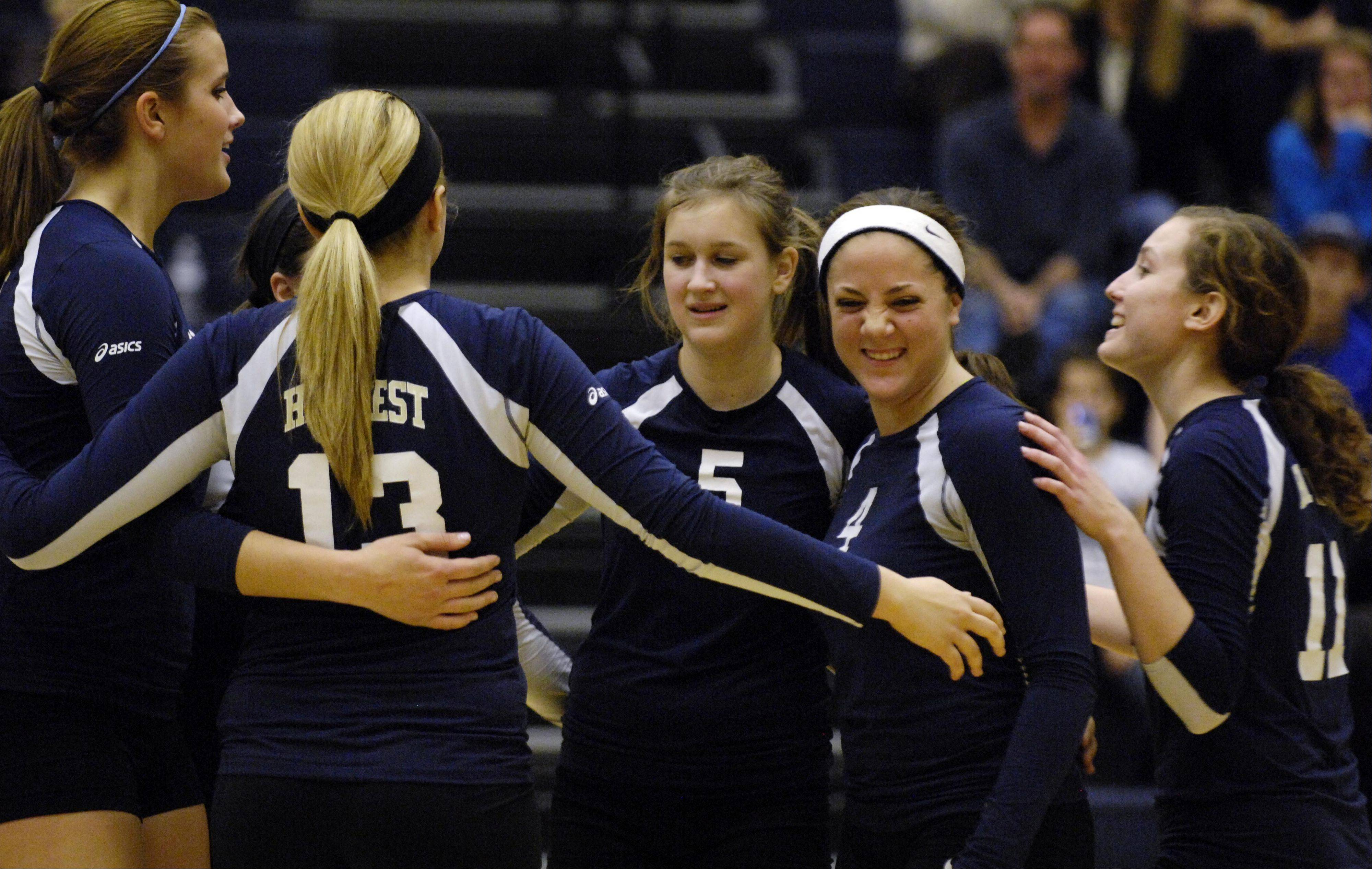 Harvest Christian Academy's Shayna Manusos (with headband) smiles with teammates as they play Chicagoland Jewish Tuesday during the sectional match in Elgin. Harvest won in two games.
