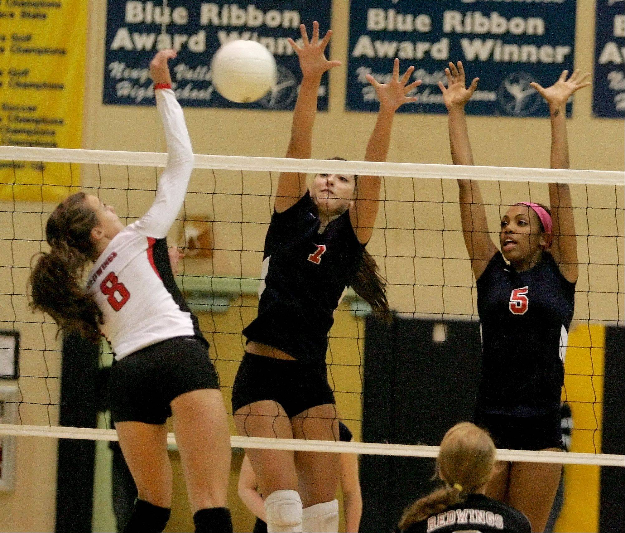Nicki Barnes, left, of Benet, spikes the ball as Demi Heiss, center, and Nerissa Vogt, right, of West Aurora go up to block in girls volleyball Neuqua Valley sectional semifinals in Naperville on Tuesday.