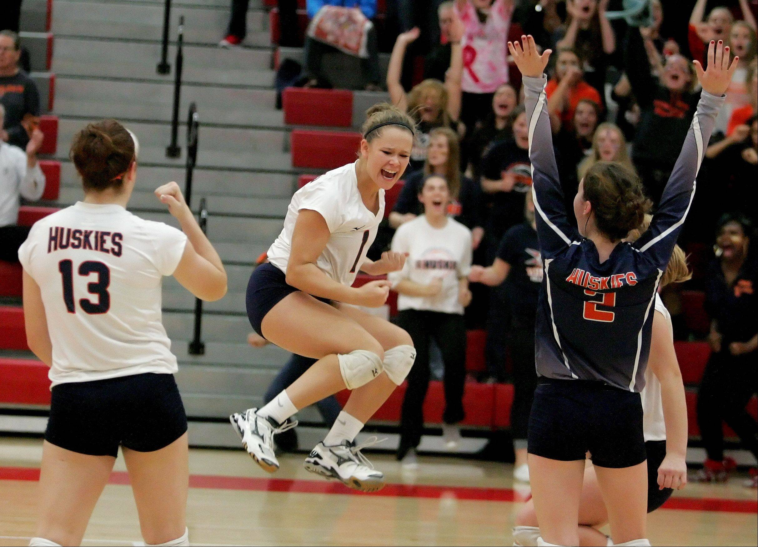 Naperville North players react to winning the first game over Neuqua Valley in Class 4A girls volleyball regional semifinals at Naperville Central on Monday. Naperville North won the match 2-0.