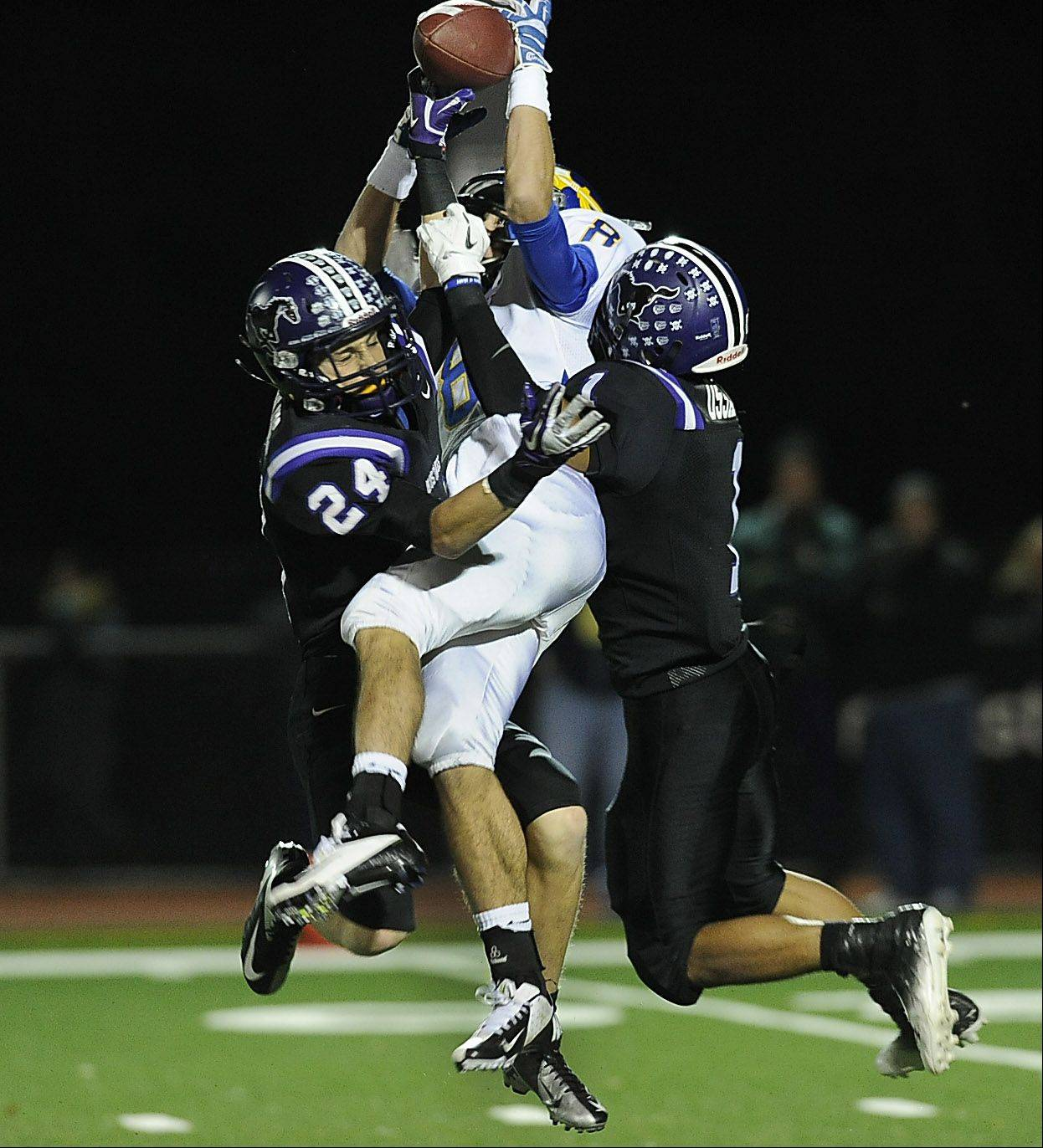 Rolling Meadow's Luke Toenjes and Christian Ossario sandwich Lake Forest's Jack Troller during a pass play in Friday's Class 6A playoff football game in Rolling Meadows.
