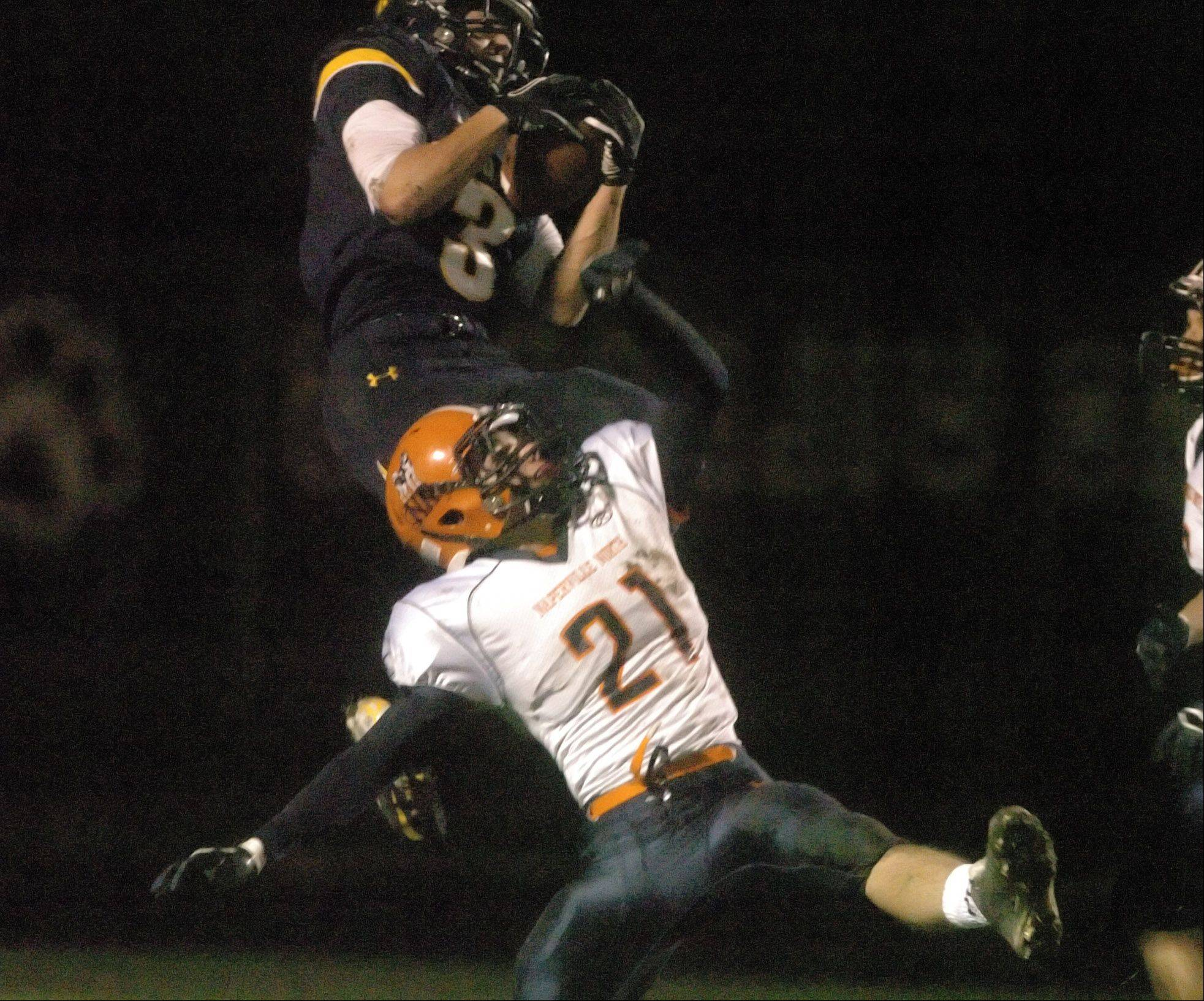 Neuqua Valley's Mikey Dudek pulls down a pass while Naperville North's Danny Schertz attempts to break up the play durying Friday's football playoff game.