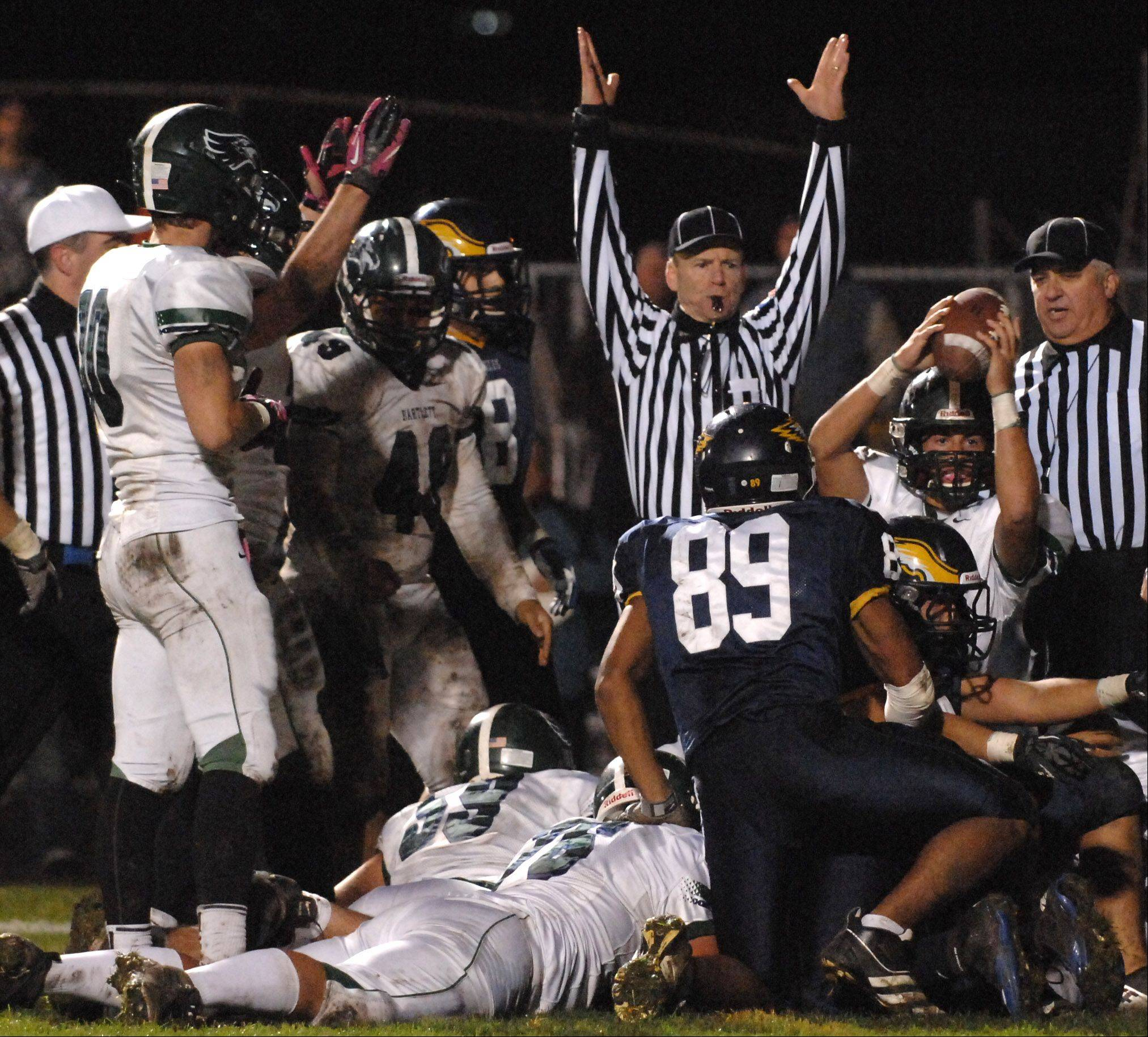 Bartlett's Kyle Garcia, 11, holds up the ball as the referee signals touchdown to put the Hawks up 14-0 over Leyden in Northlake Friday.