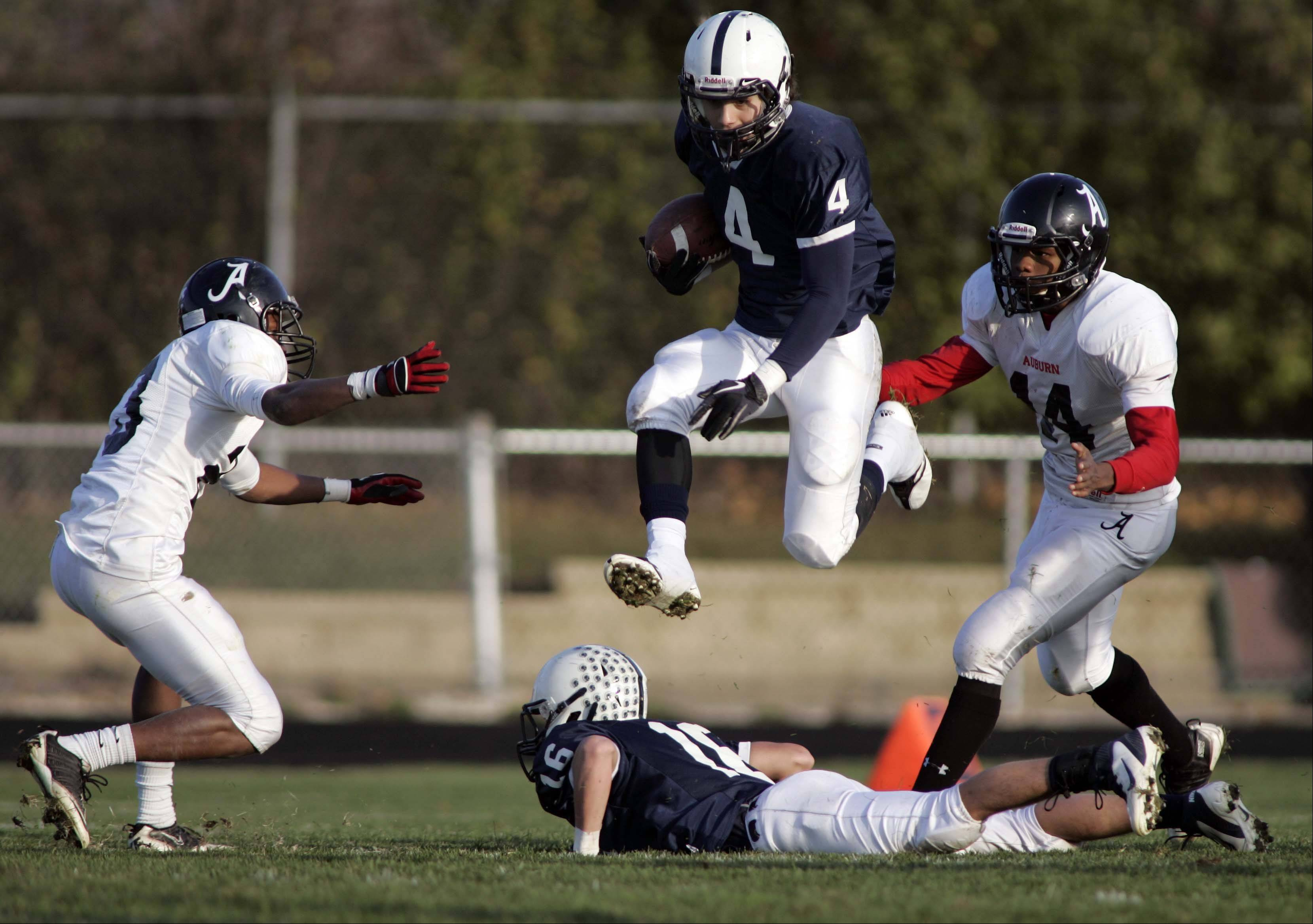 Cary-Grove's Ryan Mahoney, 4, leaps over Kaene Connington for extra yards against Rockford Auburn during Saturday's Class 6A playoff football game.