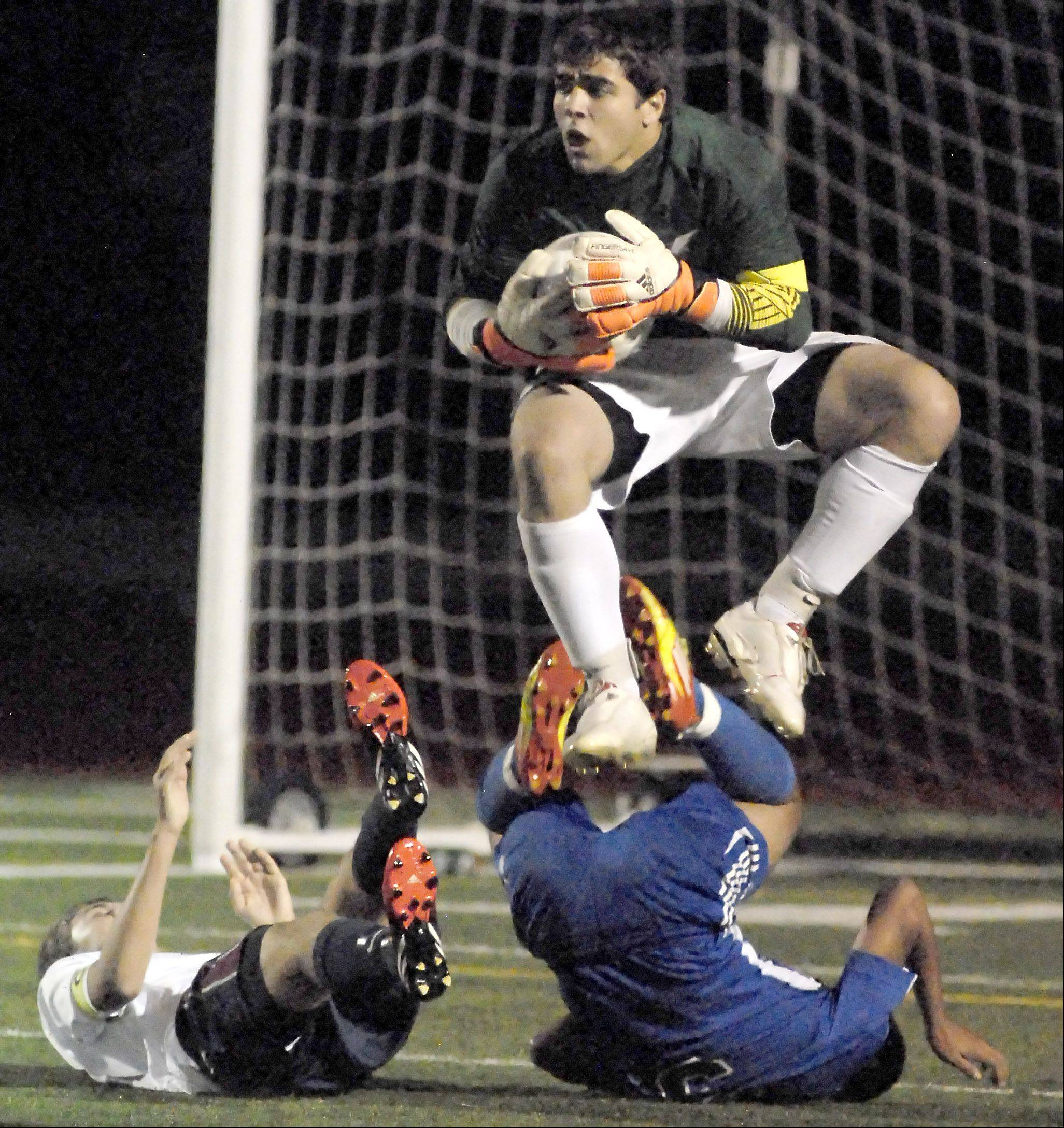 South Elgin goalie Tyler Shipon leaps in the air to avoid a collision with teammate Adam Smith and Larkin's Chris Villalobos in the first half on Tuesday.