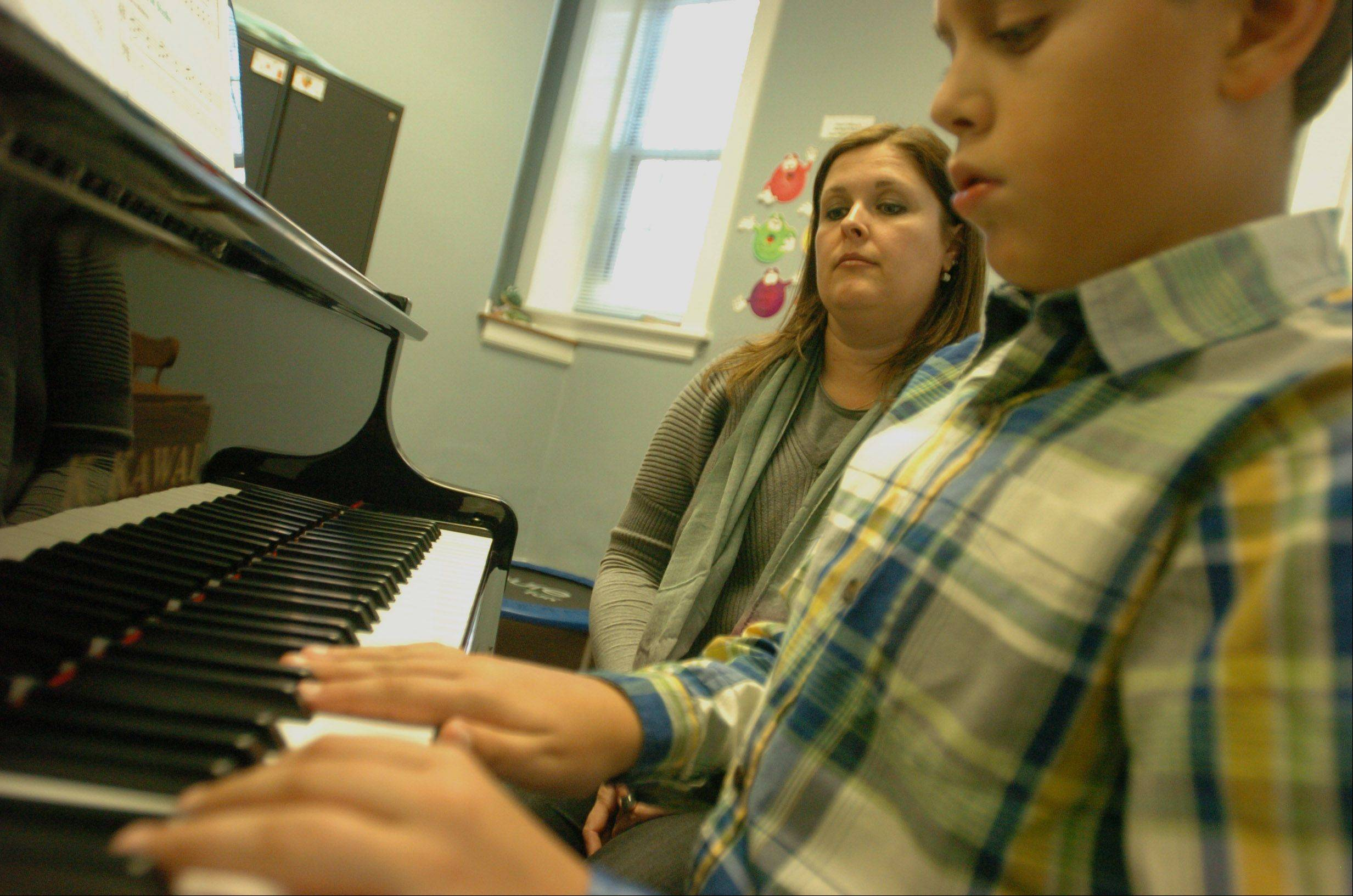 Jackson Finken works on a piece of music with his Beethoven's Buddies teacher Beth Bauer at his side. The program, operated by the Community School of the Arts at Wheaton College, teaches music to children with disabilities.