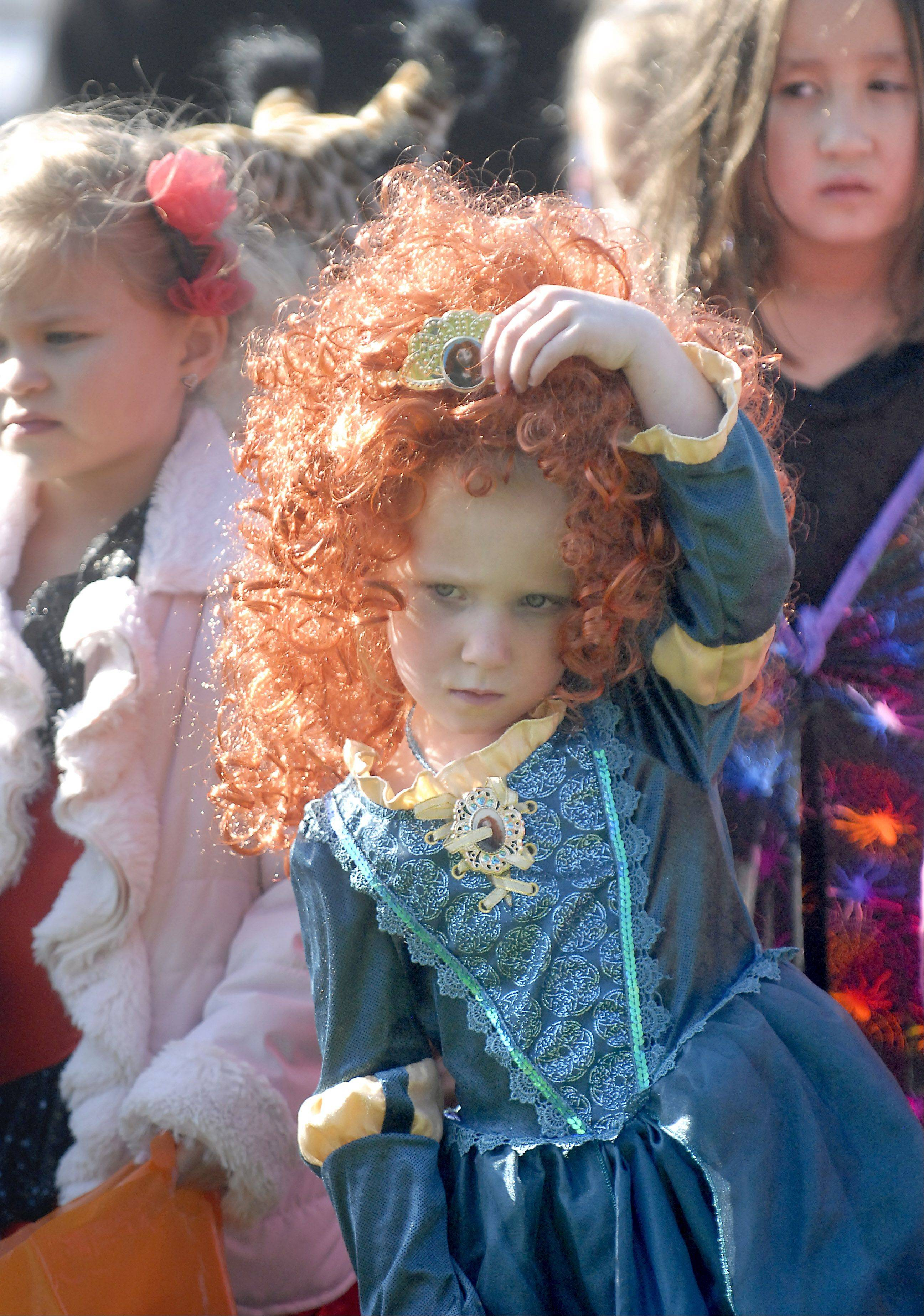 Cate Costello, 4, of Geneva, takes off her wig so it won't slow her down during the goodie-filled plastic egg hunt at Geneva Park District's Halloween Hayday at the Persinger Recreation Center on Saturday, October 27. Her costume is Merida from the Brave cartoon movie.