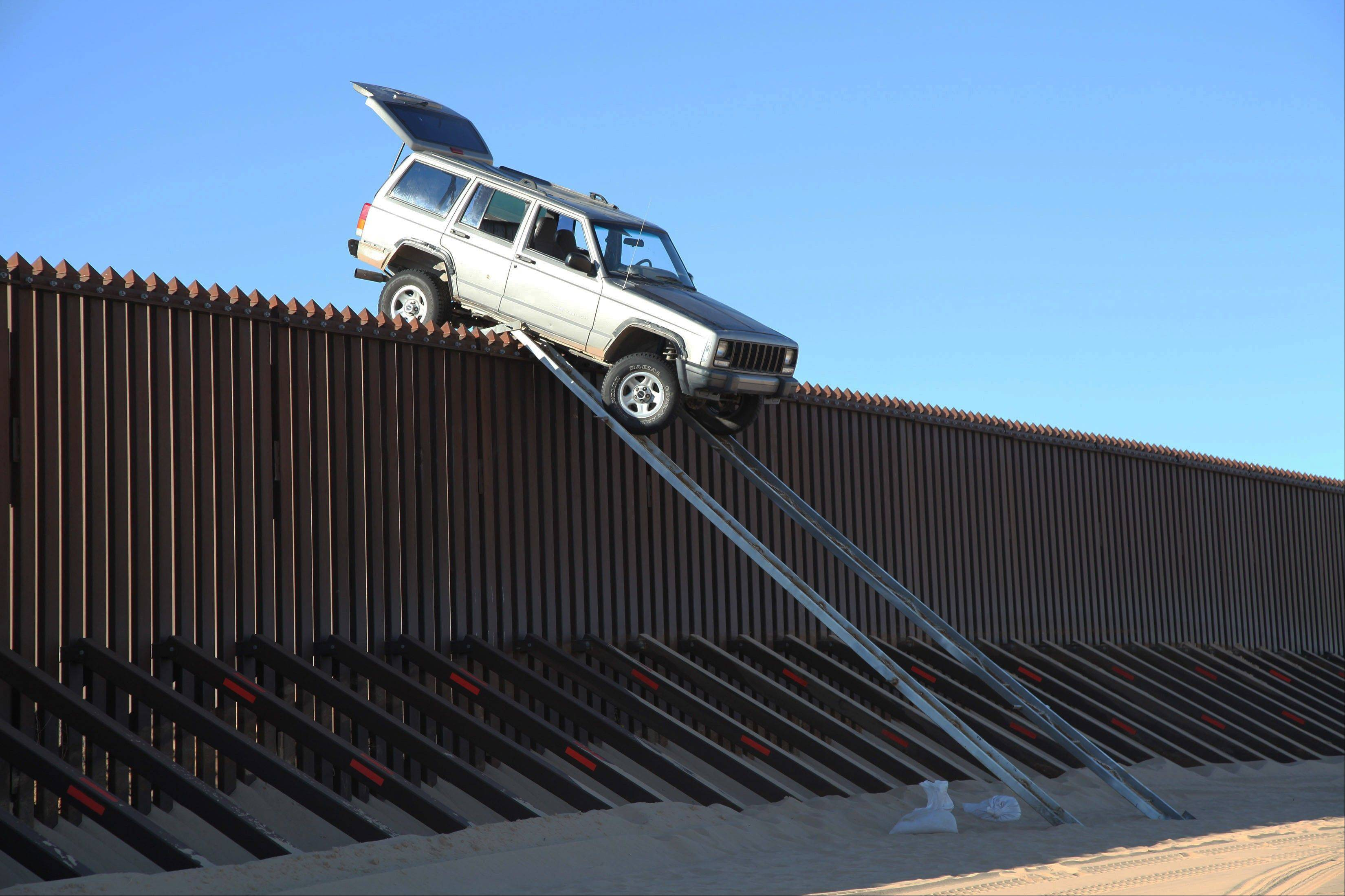 A Jeep Cherokee that suspected smugglers were attempting to drive over the U.S.-Mexico border fence got stuck at the top of a makeshift ramp early Wednesday near Yuma, Ariz.