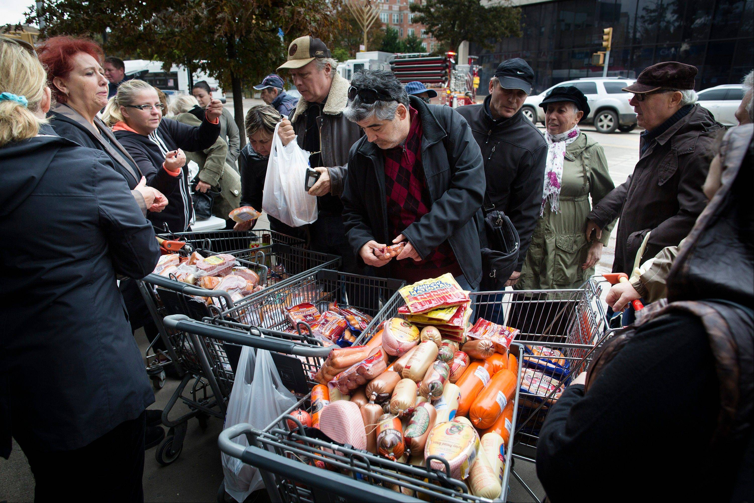 People shop for food piled into shopping carts Wednesday in Brooklyn. People in the coastal corridor battered by superstorm Sandy took the first cautious steps Wednesday to reclaim routines upended by the disaster, even as rescuers combed neighborhoods strewn with debris and scarred by floods and fire.
