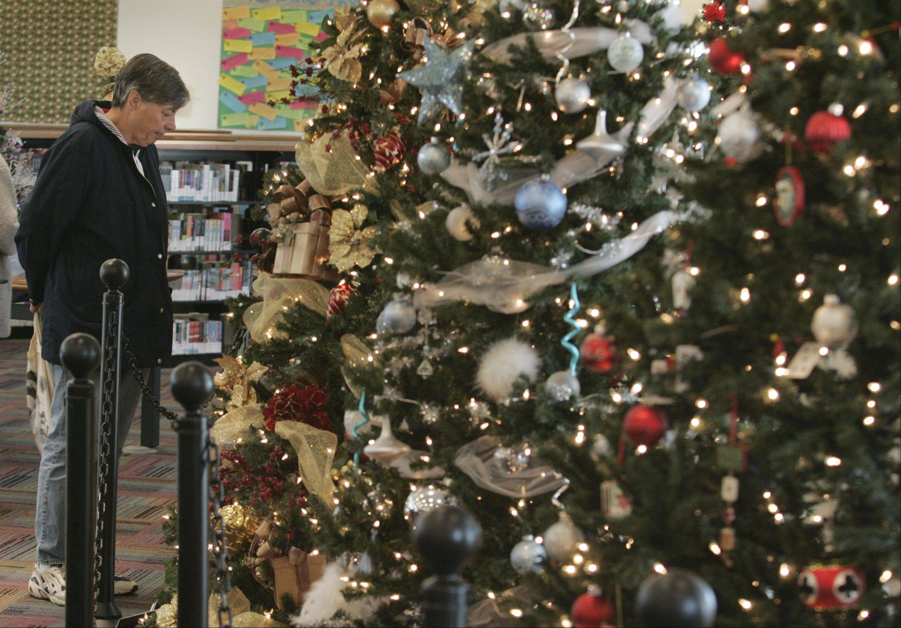 Rosemary Holland of Elgin takes a look at the 2006 Festival of Trees display at the Gail Borden Public Library. The exhibit, which moved from its former location at the Elgin Police Department, features trees sponsored by local businesses to benefit the Ecker Center for Mental Health.