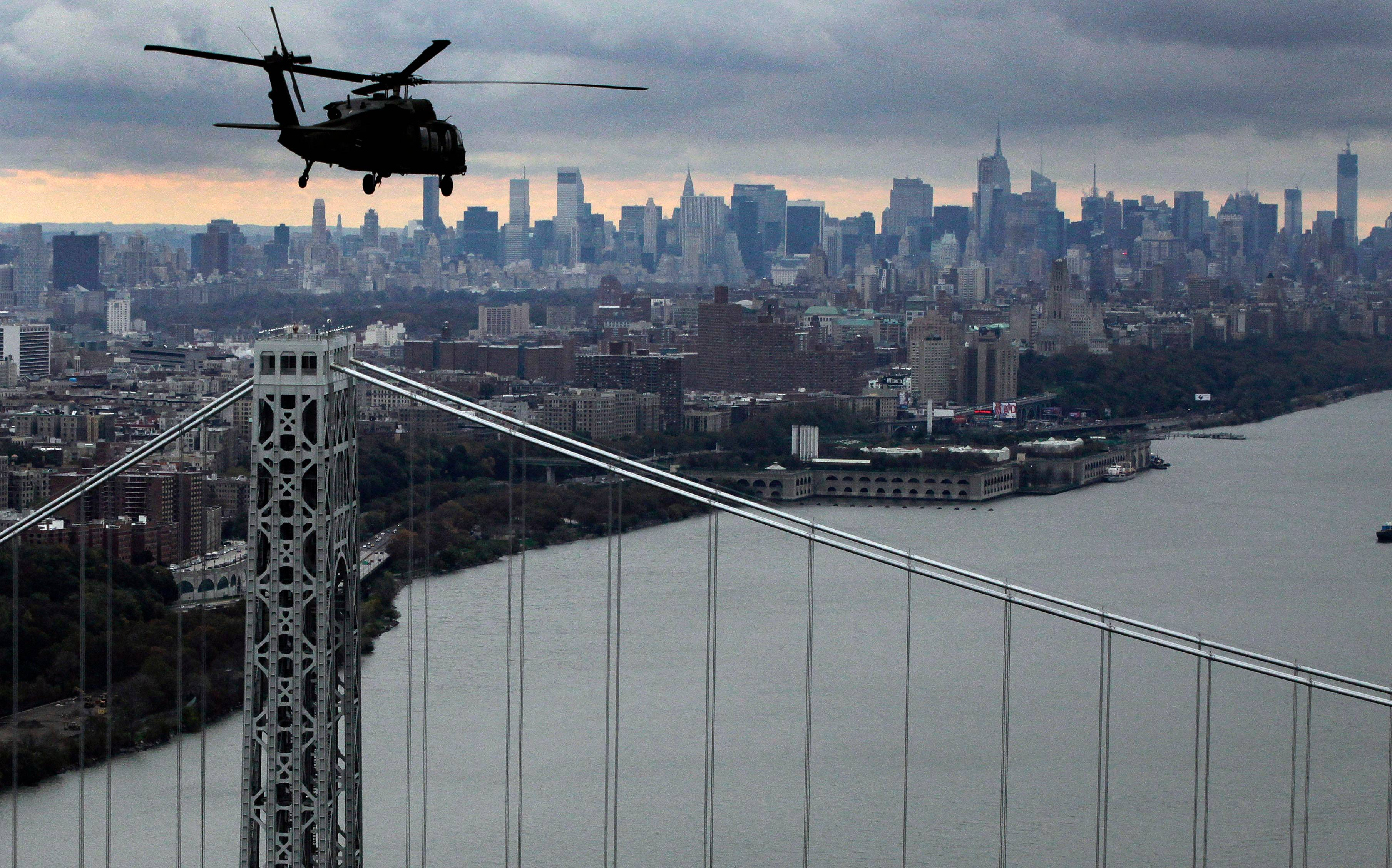 A New York Air National Guard helicopter flies above the George Washington Bridge towards Manhattan, Wednesday, Oct. 31, 2012 in New York. Gov. Andrew Cuomo, Sen. Kirsten Gillibrand, D-NY, Sen. Charles Schumer, D-NY, and local officials took the flight over the city, Nassau and Westchester counties to get an assessment of damages from superstorm Sandy.