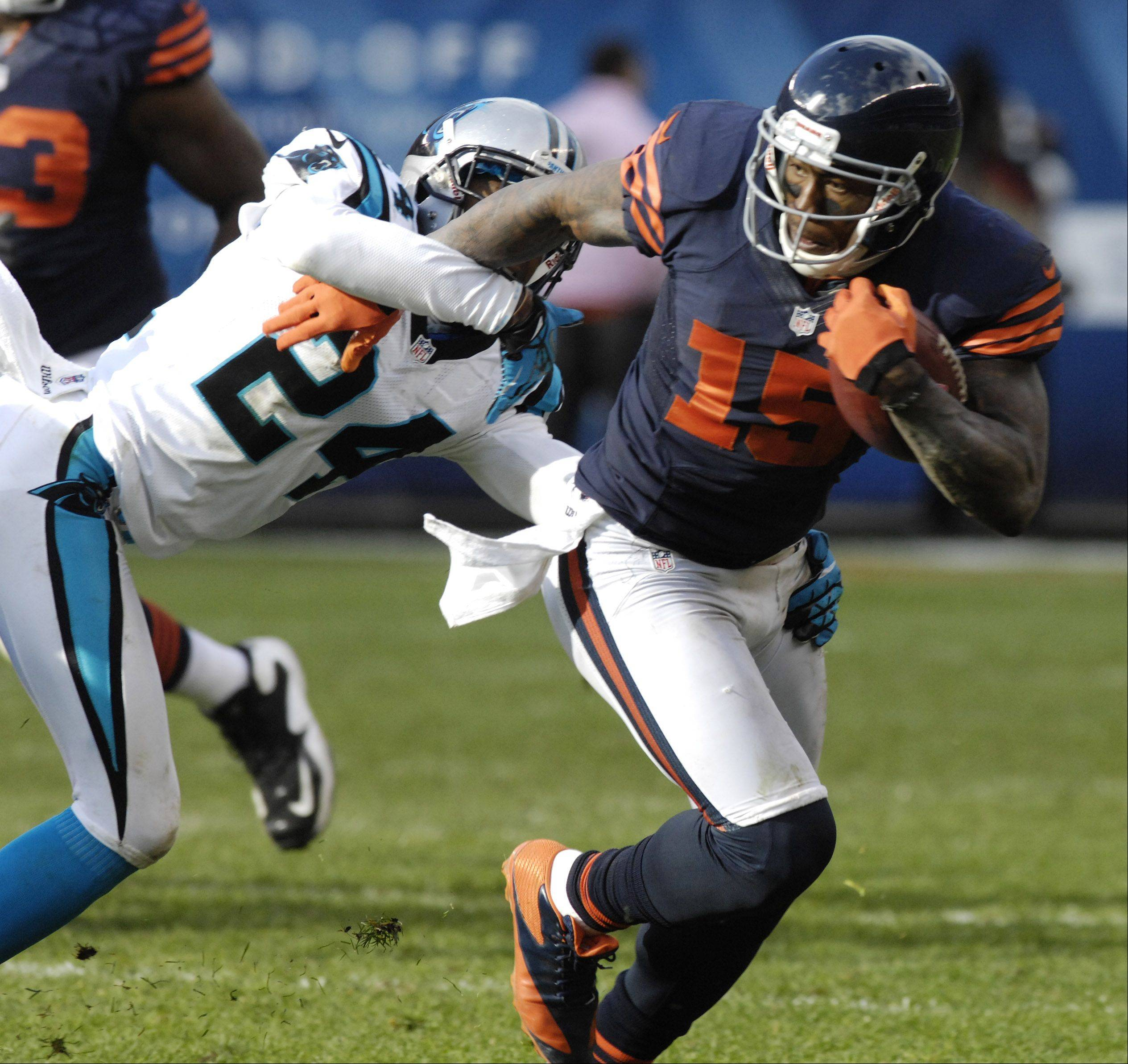 Bears wide receiver Brandon Marshall helps his team get within field-goal range while being pursued by Carolina Panthers defensive back Josh Norman during Sunday�s game at Soldier Field.