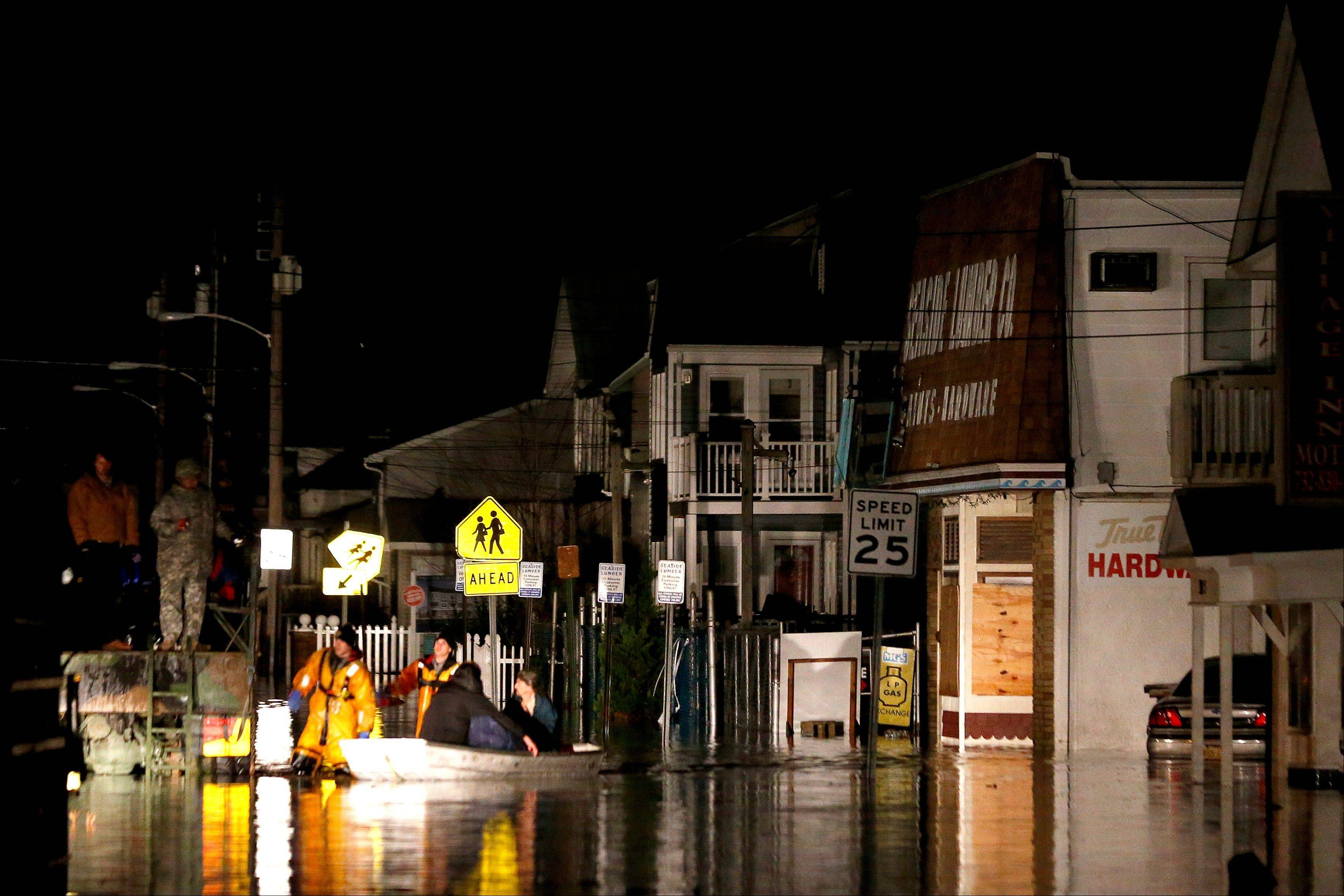 Rescue workers help stranded people out of their flooded homes in Seaside Heights, N.J., following the arrival of Superstorm Sandy, Tuesday.