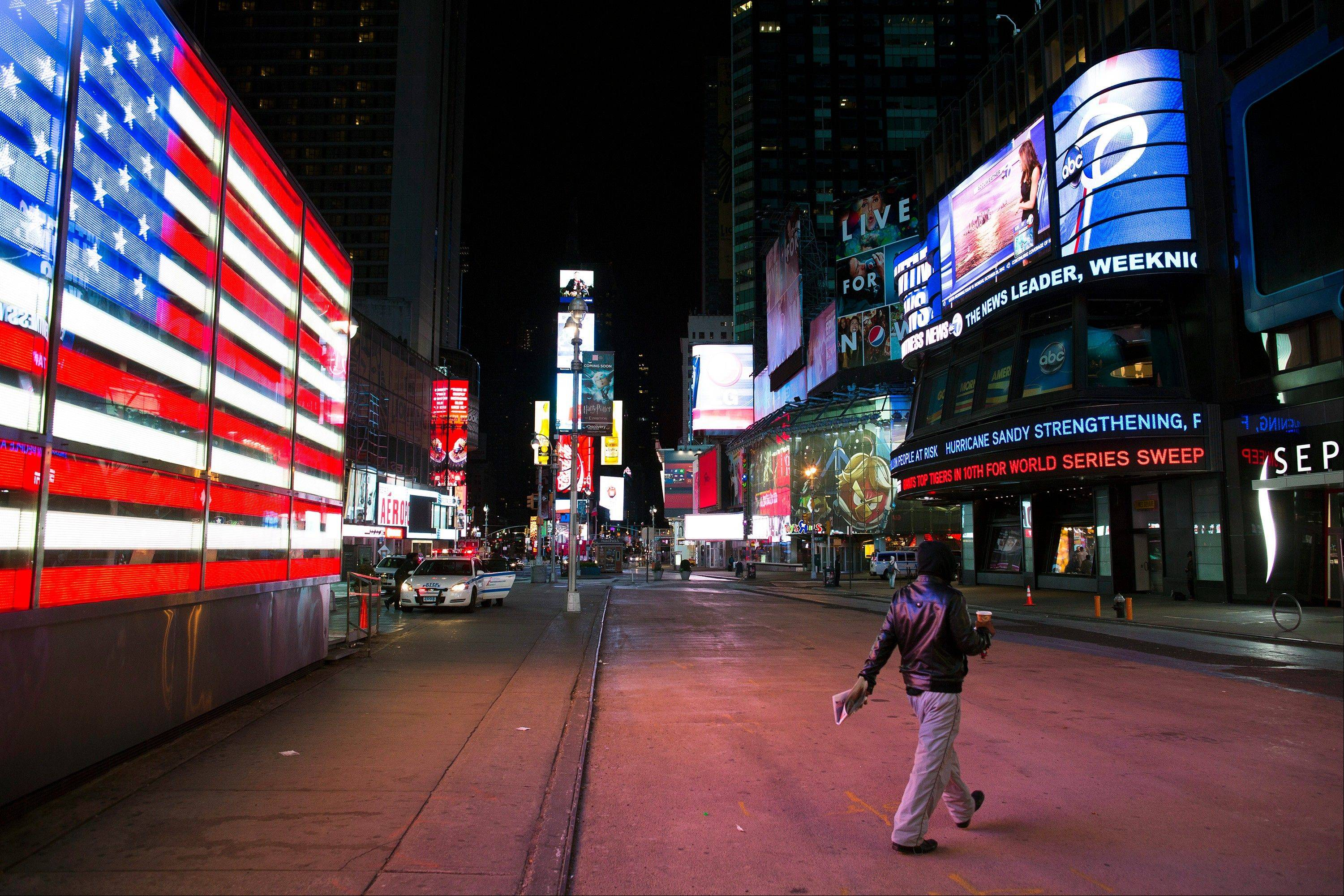 A lone pedestrian walks through an empty Times Square early, Monday in New York. Hurricane Sandy shut down a lot of entertainment events in New York Monday and Tuesday.
