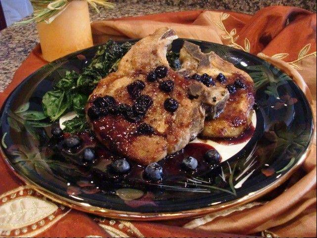 Seared pork chops sit on a bed of roasted kale; a sherry-infused blueberry sauce dresses the plate.
