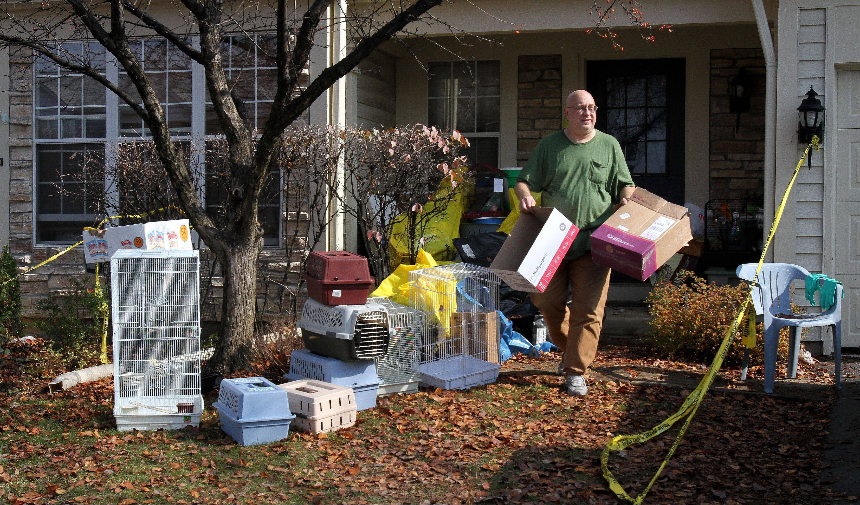 Dave Skeberdis, 57, of Aurora, removes items from his home, which housed 478 birds -- 120 of them dead -- as well as piles of garbage and bird feces three feet deep. People for the Ethical Treatment of Animals now is pushing the city of Aurora to press criminal charges against Skeberdis for cruelty to animals.