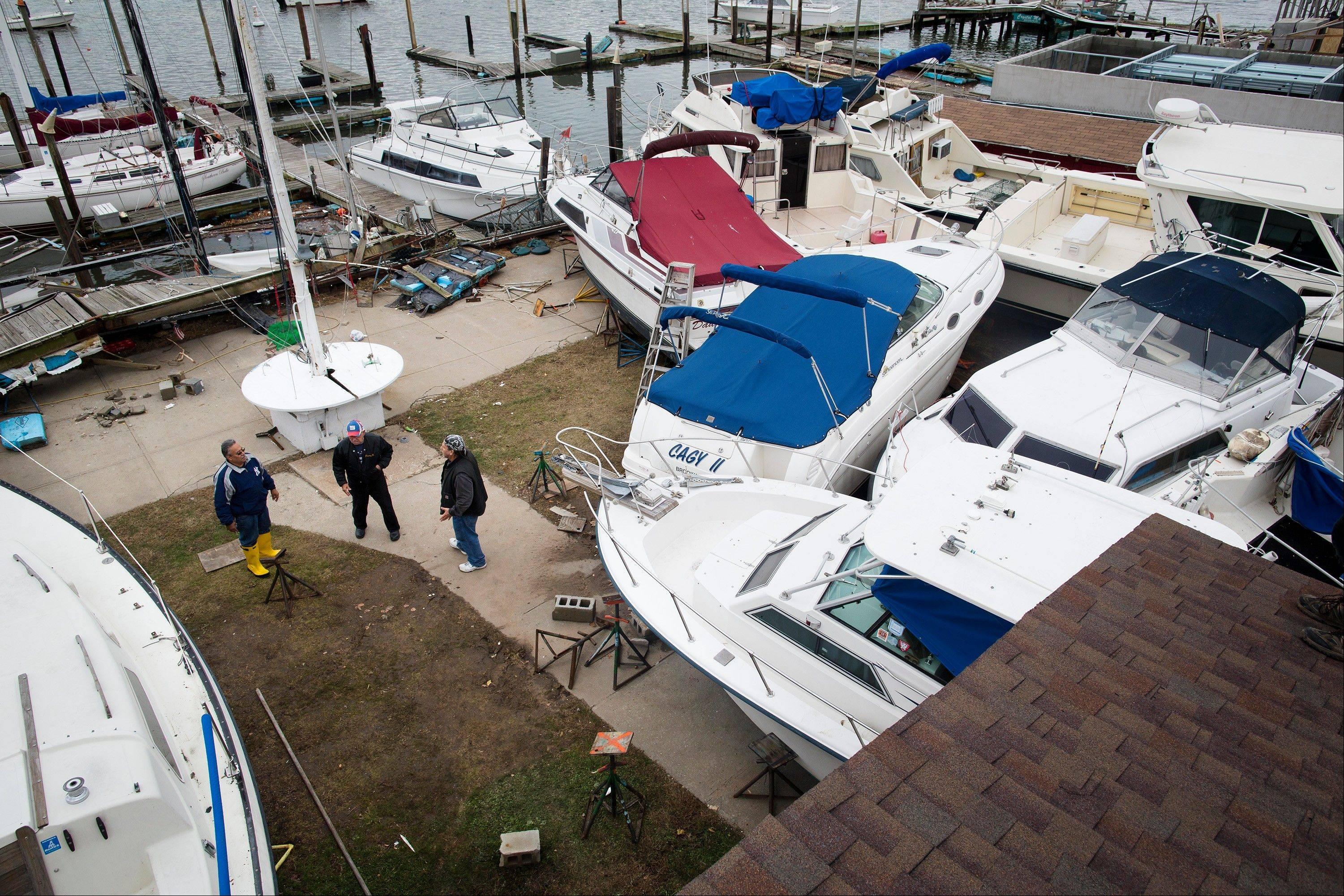 Members of the Varuna boat club stand near a pile of boats washed ashore, Wednesday, Oct. 31, 2012, in the Brooklyn borough of New York. Sandy, the storm that made landfall Monday, caused multiple fatalities, halted mass transit and cut power to more than 6 million homes and businesses.